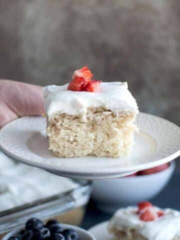 Hand holding white plate with vegan Tres Leche cake
