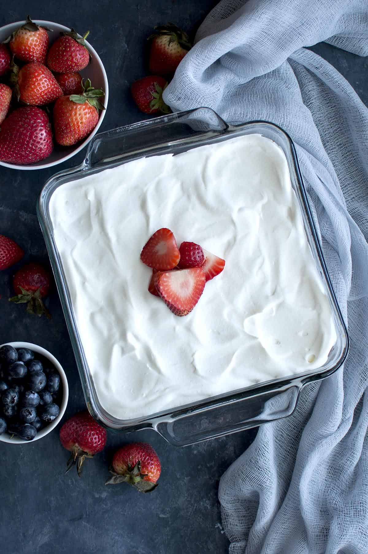 Glass square baking pan with whipped cream and sliced strawberry topped cake