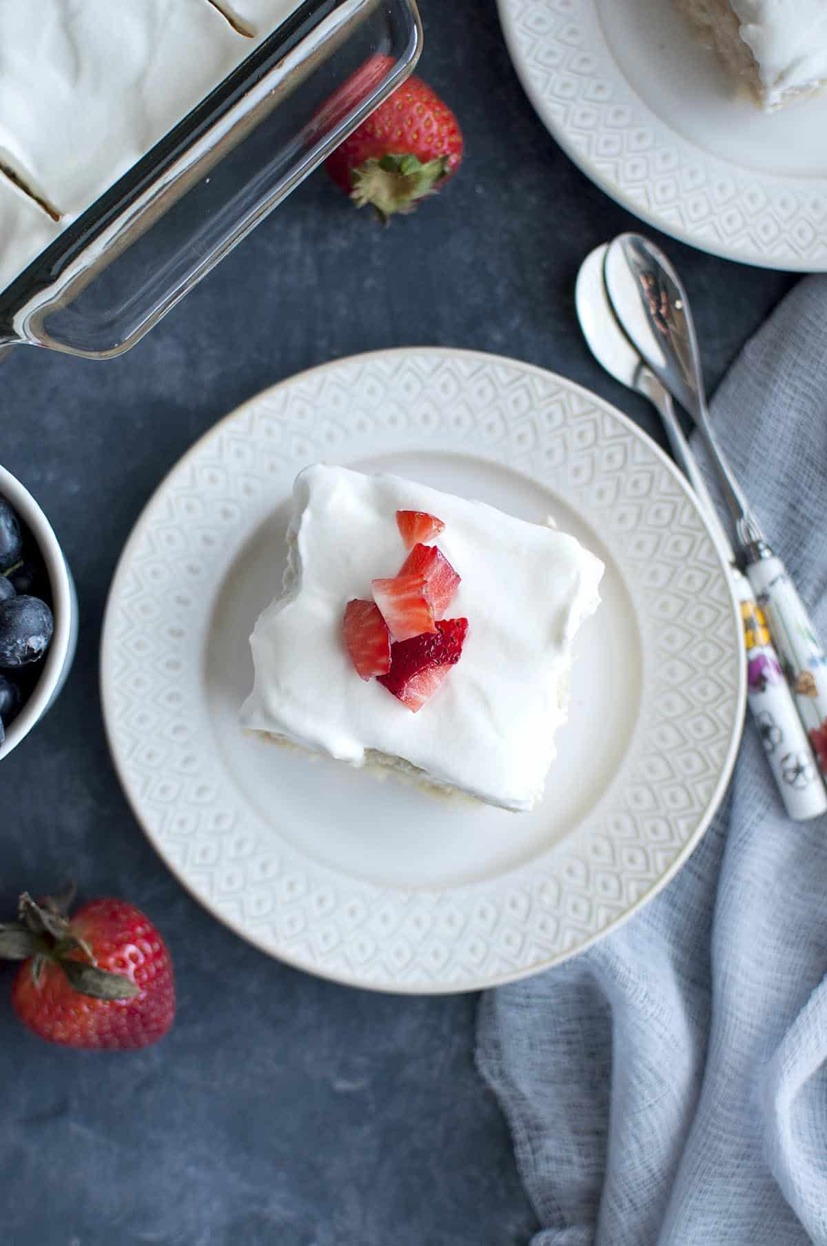 Top view of a white plate with vegan tres leche cake topped with whipped cream and chopped berries