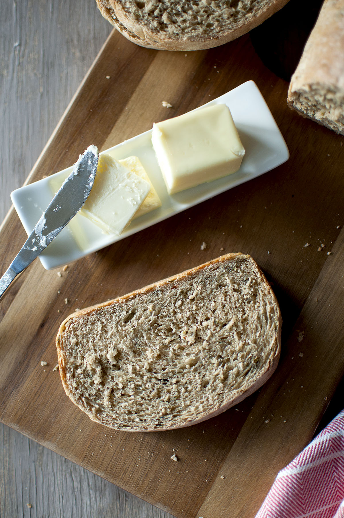 chopping board with sliced khara bread and a butter plate with butter and knife