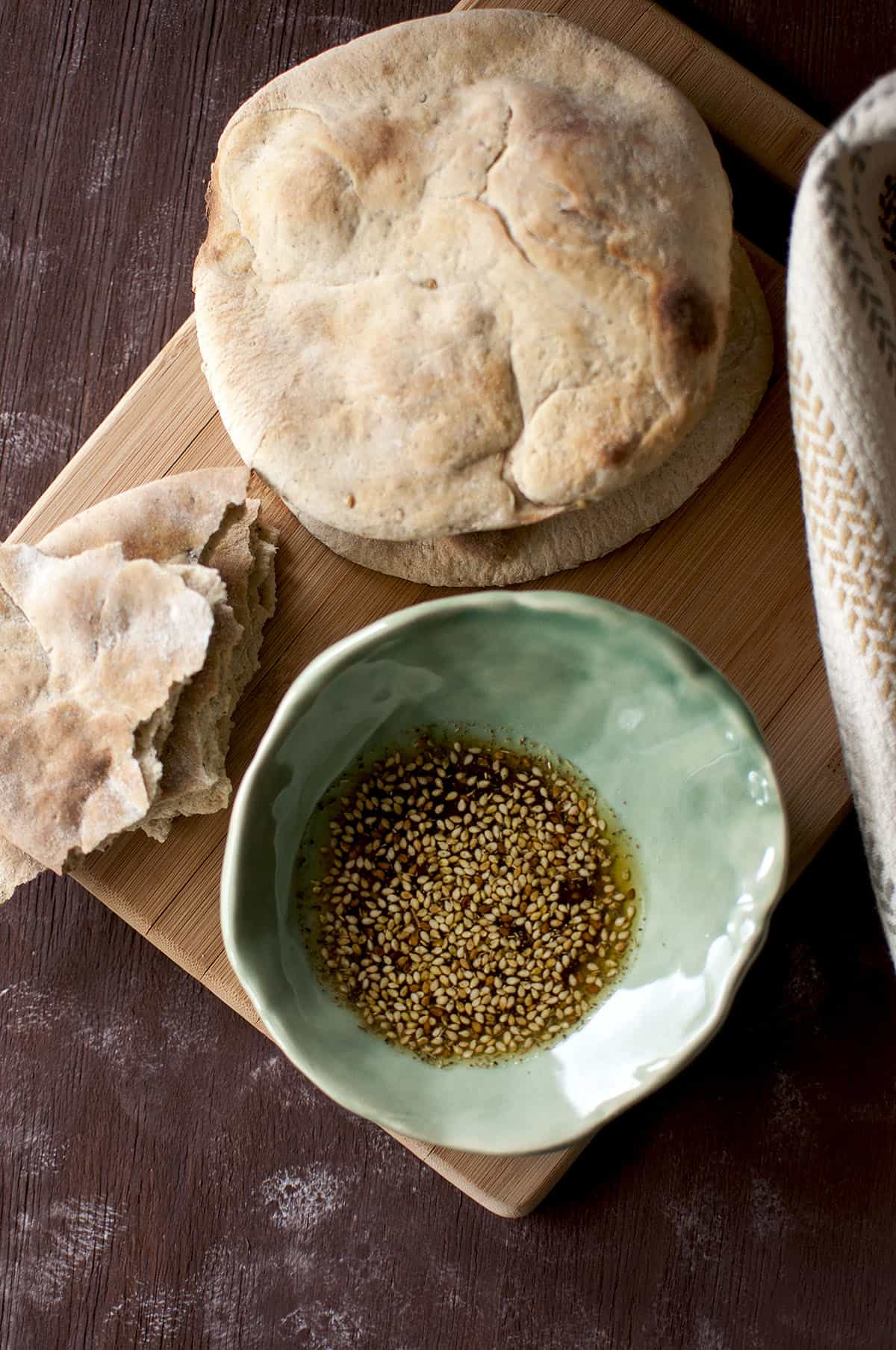Chopping board with Khobez and a green bowl with za'atar olive oil