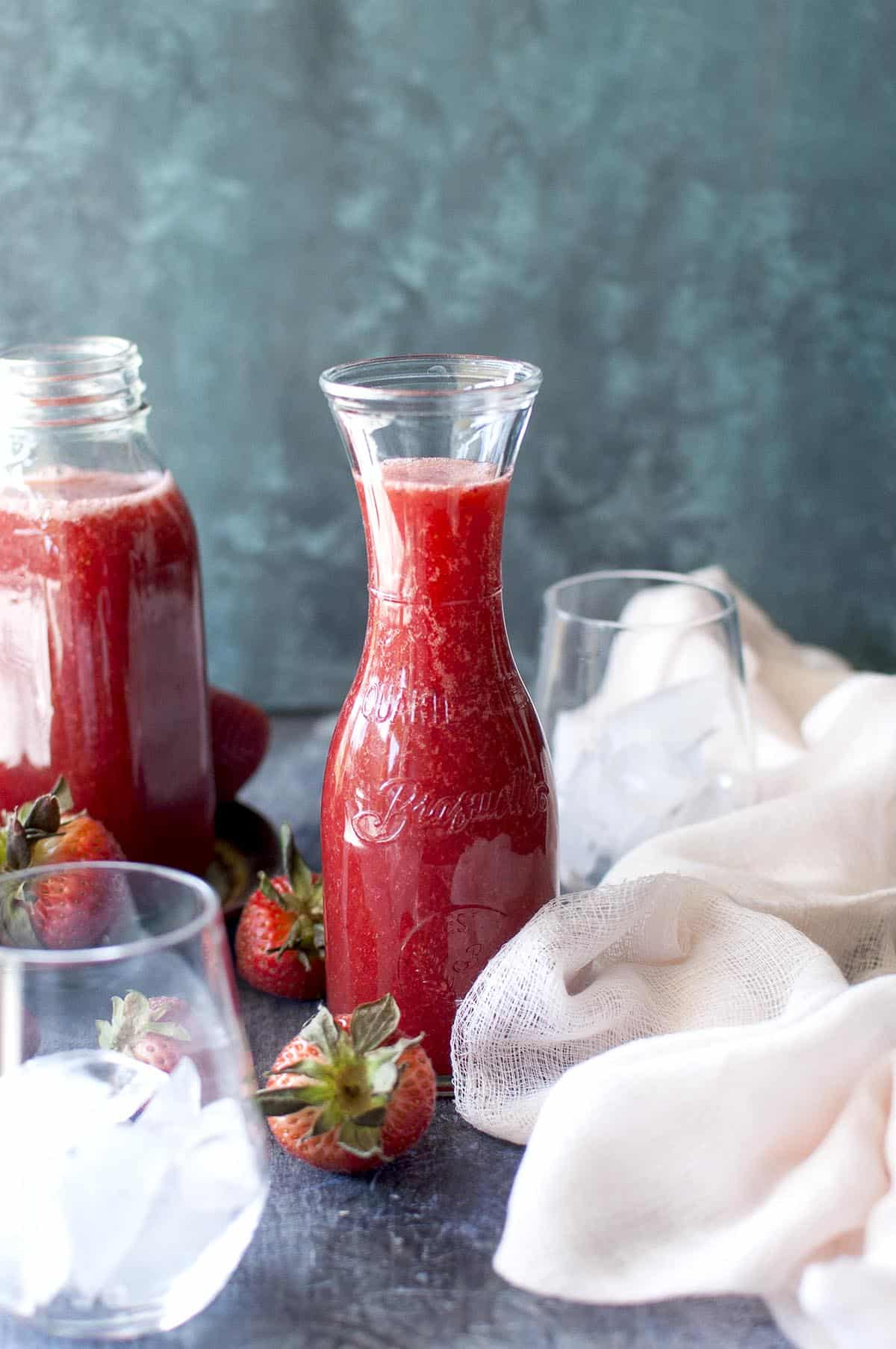 2 glass jars with strawberry crush with fresh berries on the board