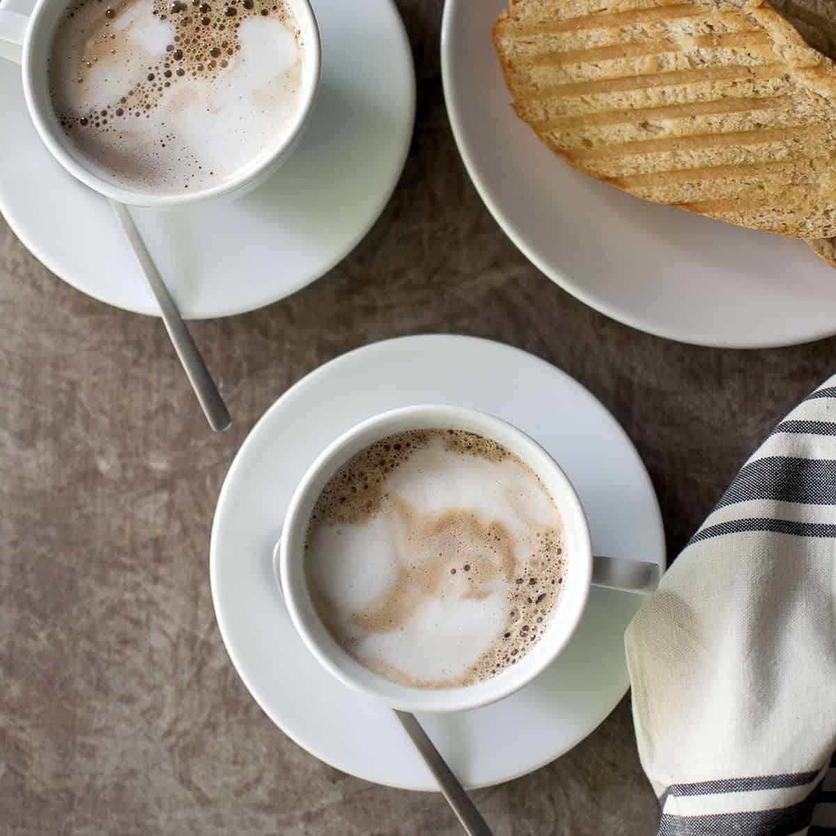 Two white cups with espresso and toast in the background