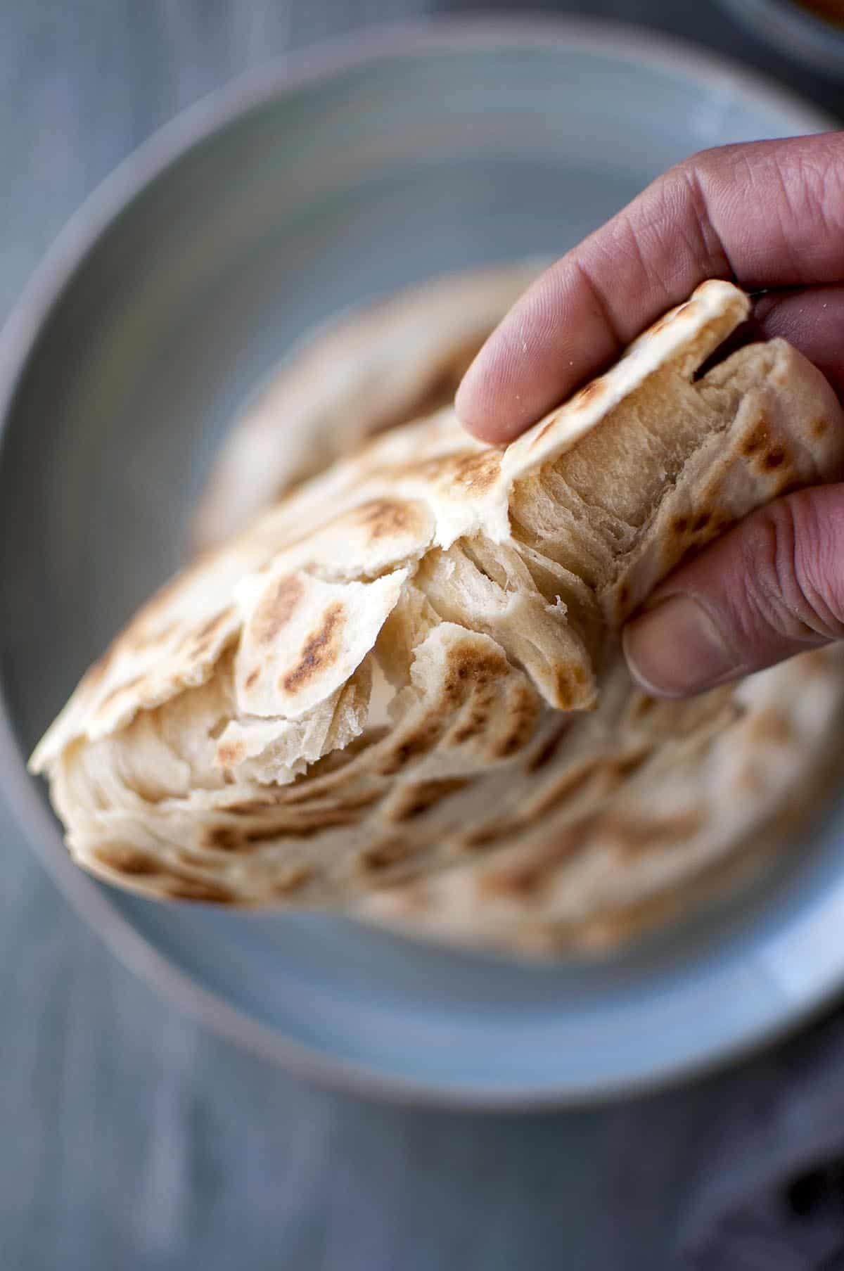 hand holding flaky Malaysian roti canai