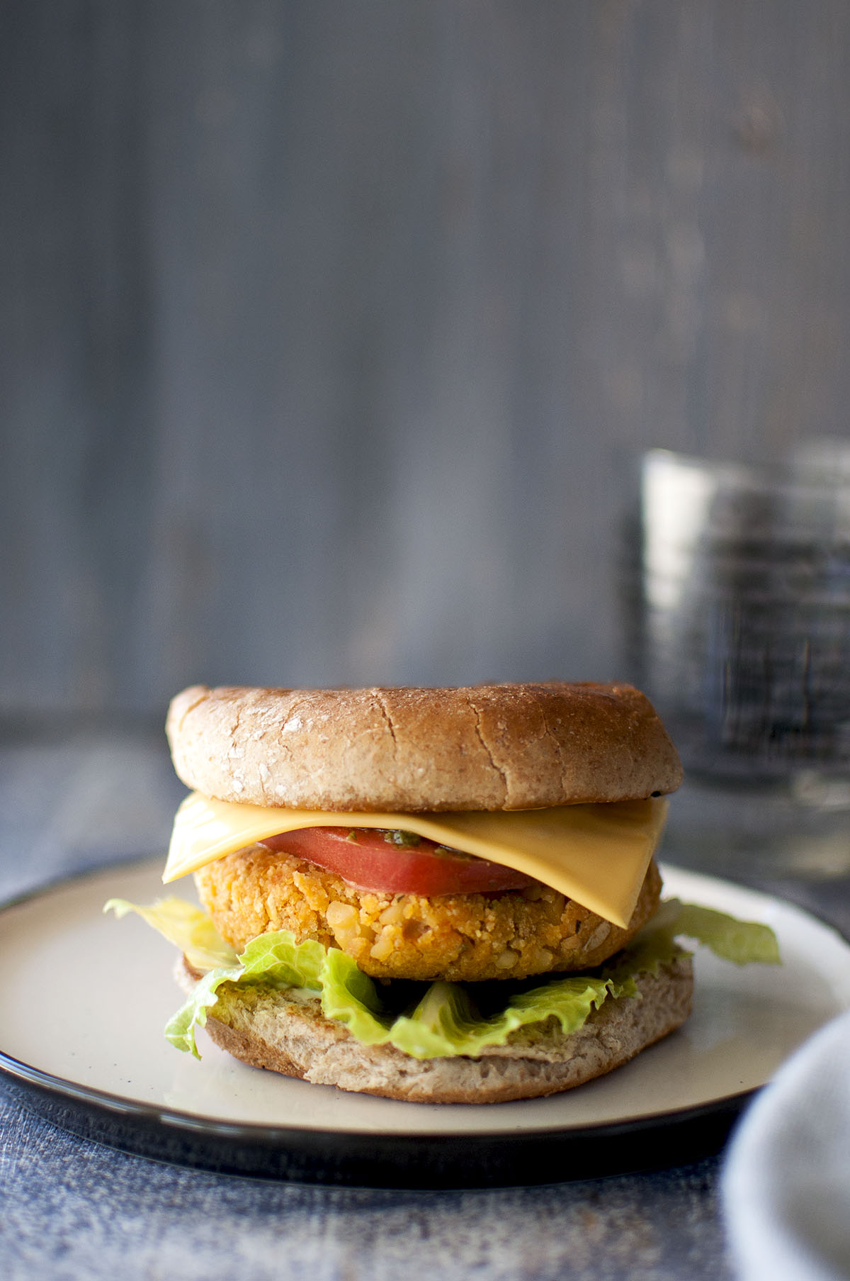 White plate with Sweet potato chickpea burger sandwich with lettuce, tomato and cheese
