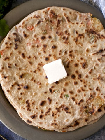 Grey plate with Navratan Paratha topped with a dab of butter