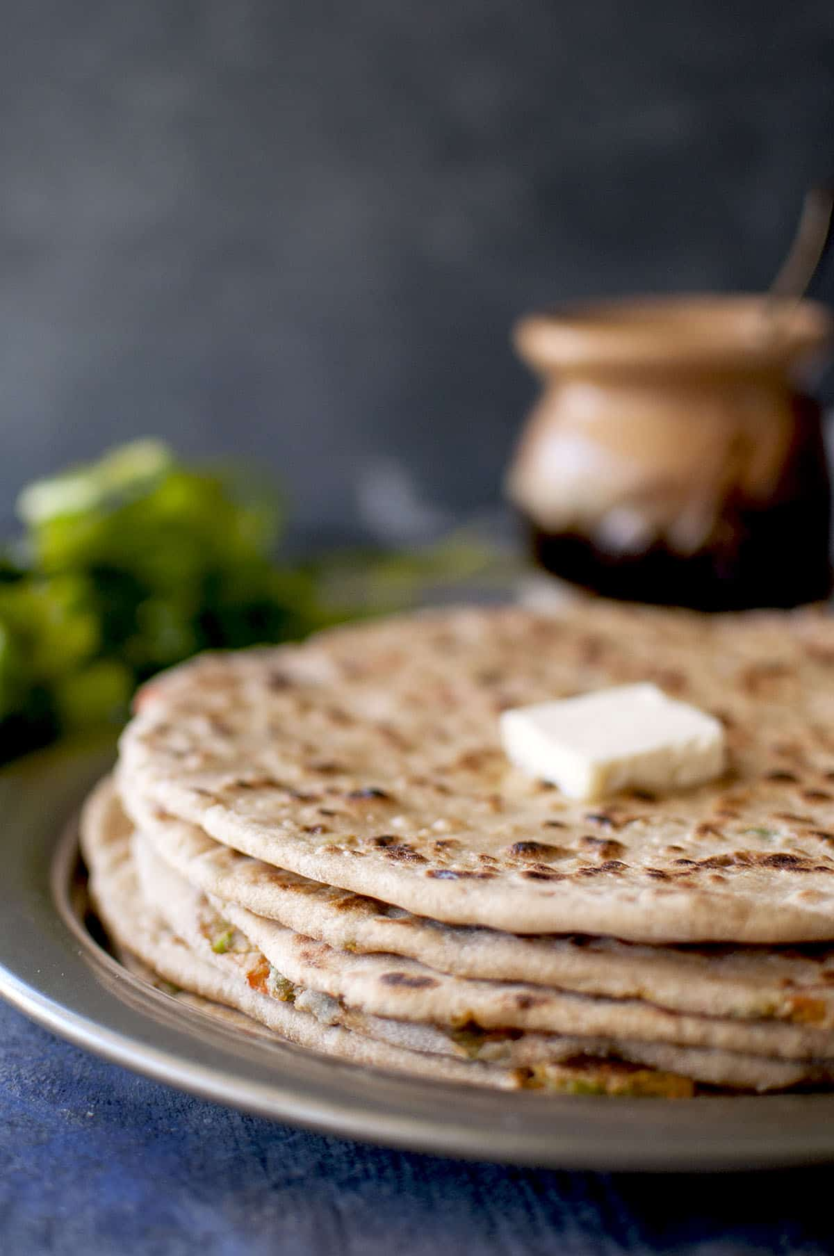 Grey plate with a stack of navratan paratha and a dab of butter on top