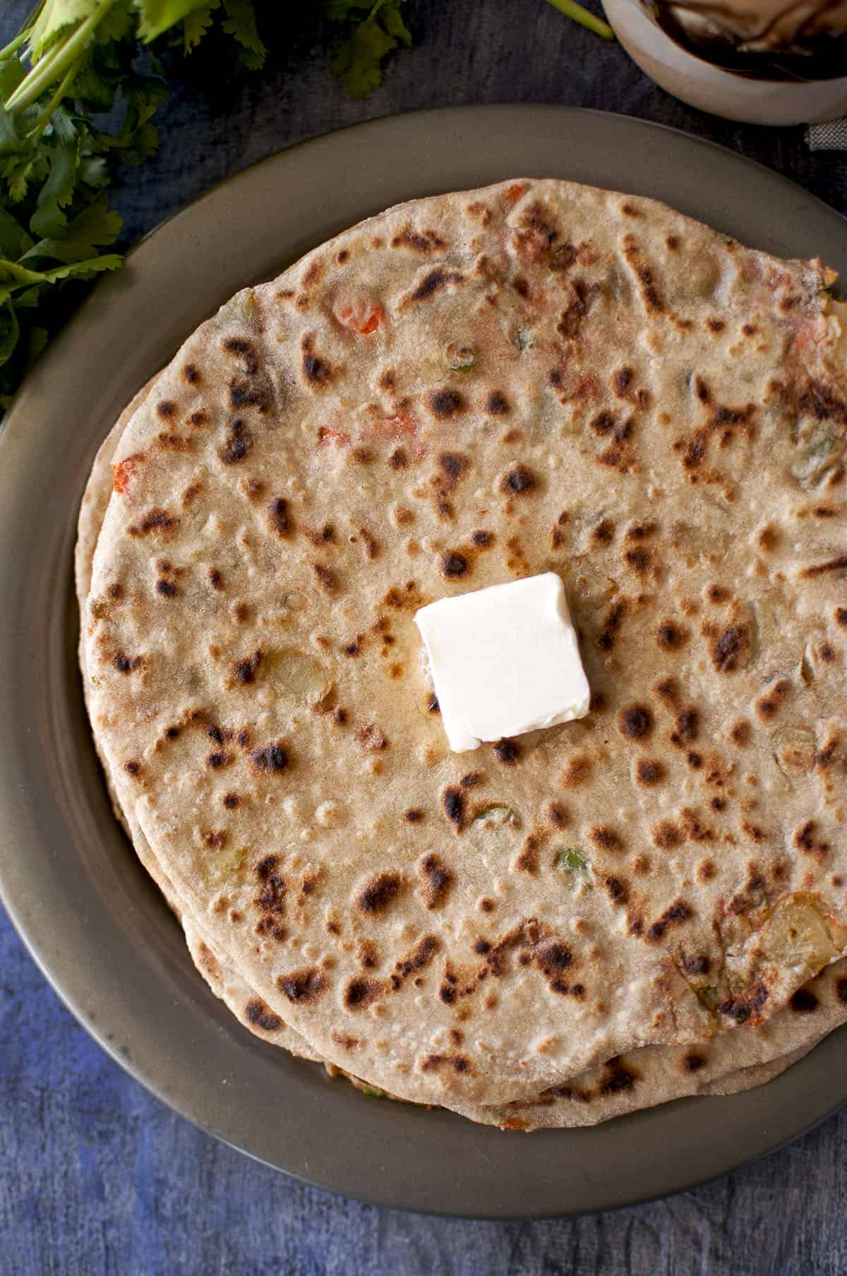 Grey plate with Navaratna paratha with a dab of butter on top