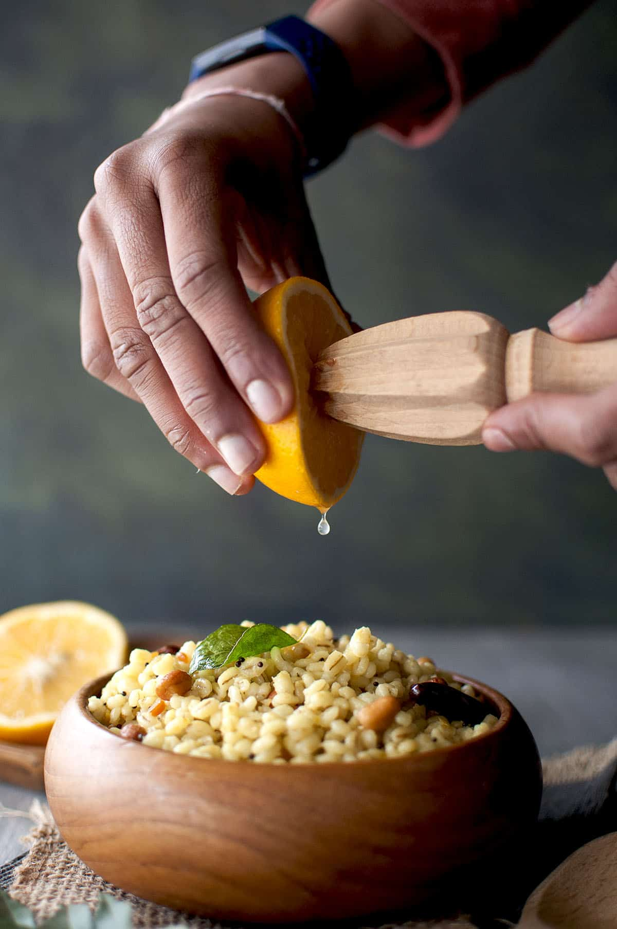 Hand squeezing lemon juice into a wooden bowl