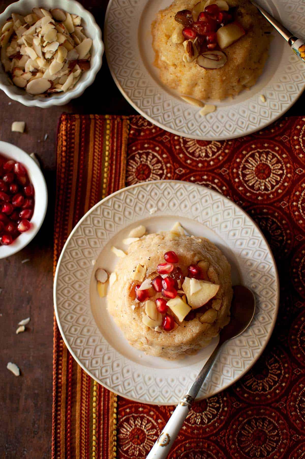White plate with Jonna rava kesari topped with fruit