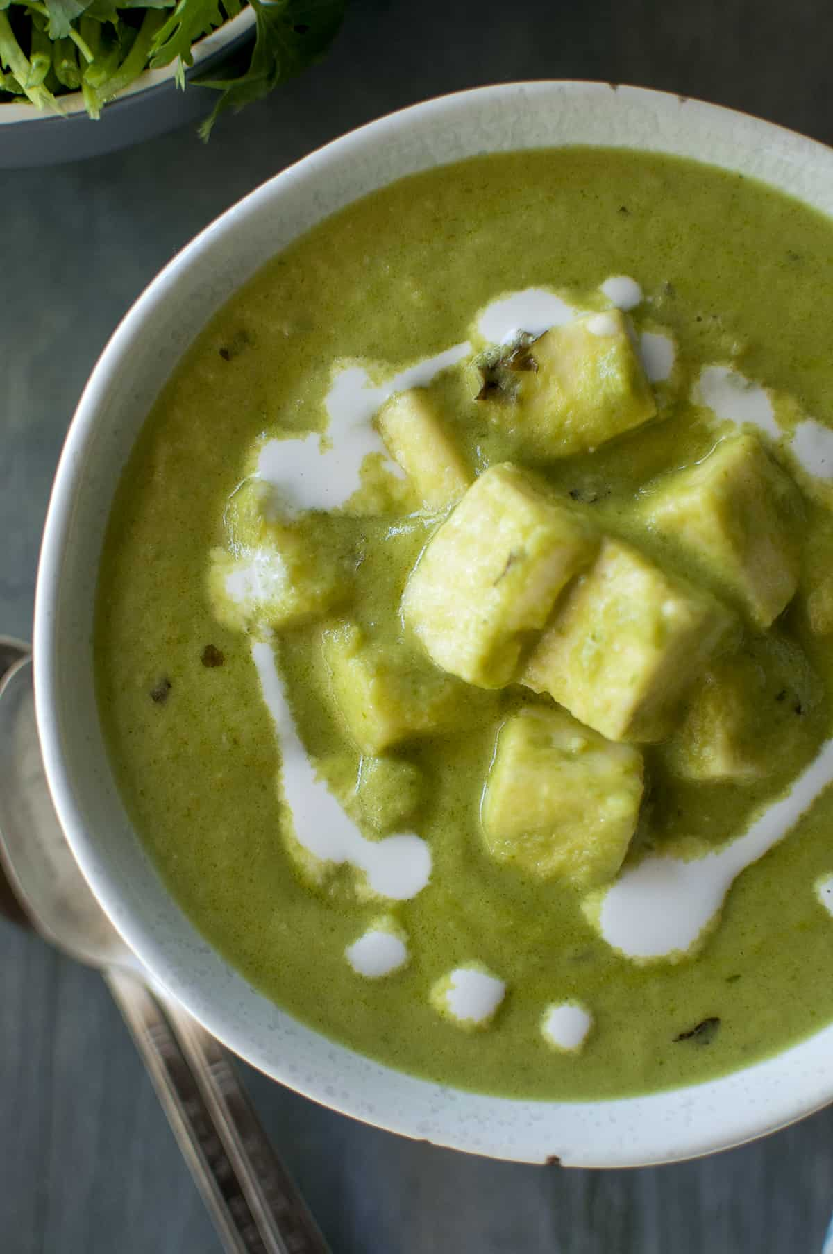 Grey bowl with green paneer curry