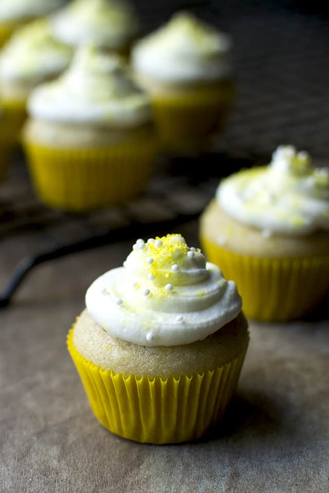 Vegan lemon cupcake in a yellow cupcake liner topped with frosting and sprinkles