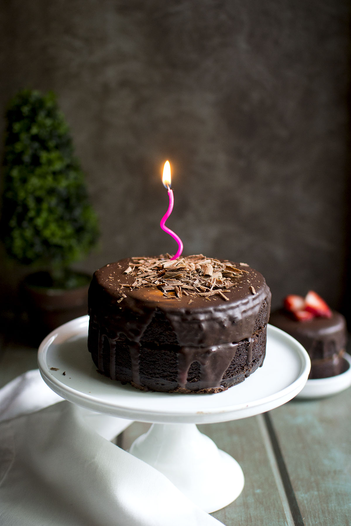 White cake stand with vegan chocolate cake with a lit candle on top
