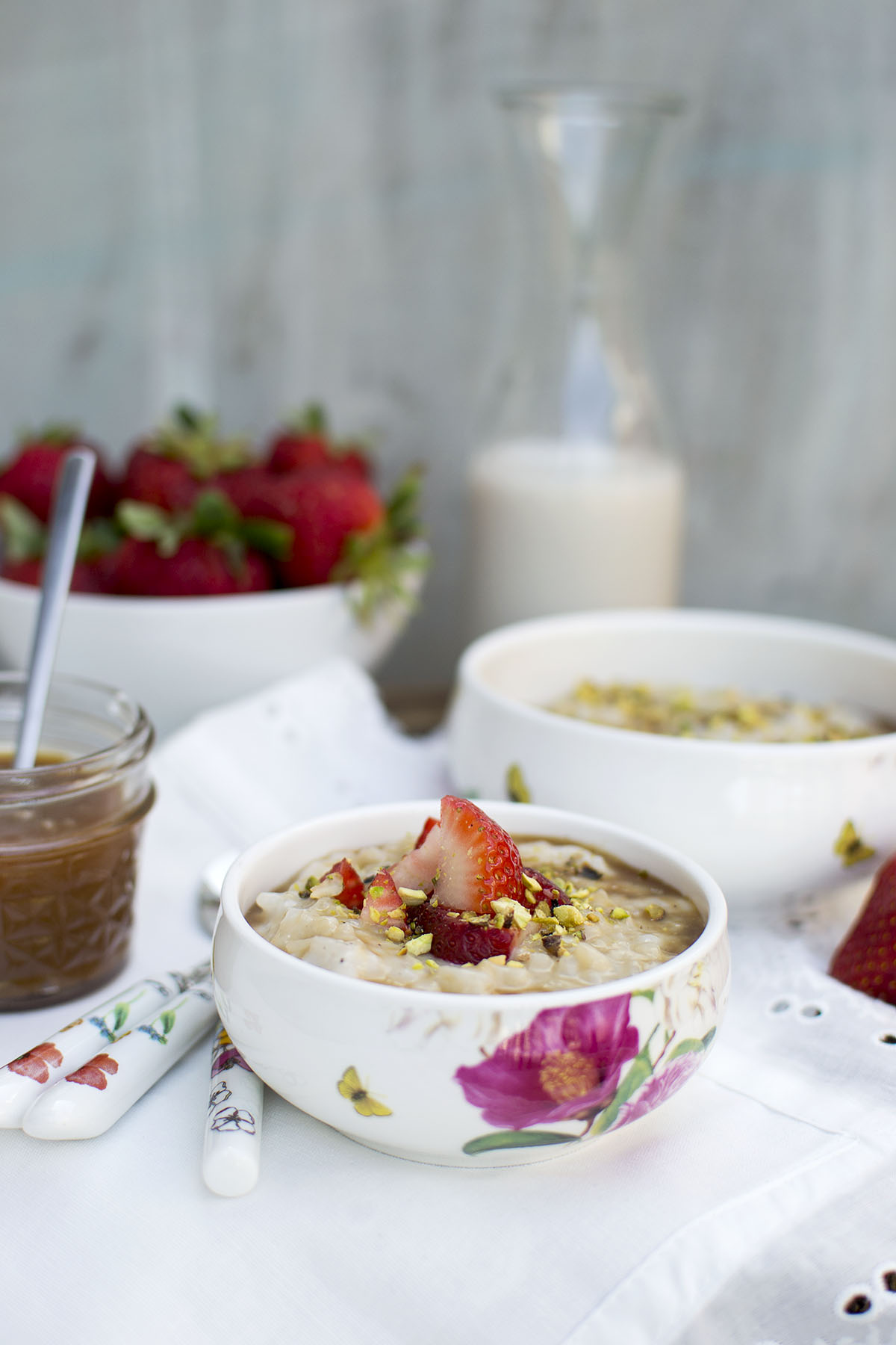 White bowl with rice pudding topped with chopped berries and nuts