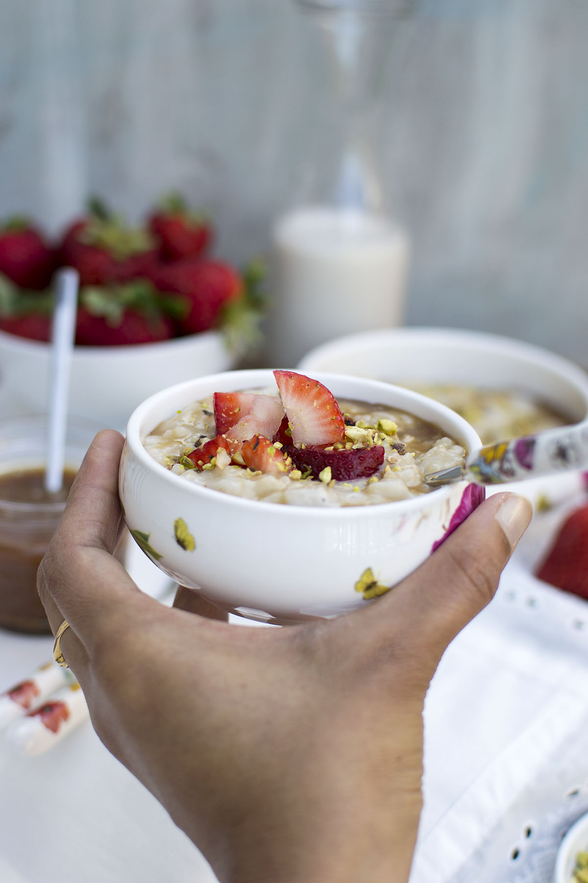 Hand holding a bowl with dessert topped with berries and nuts