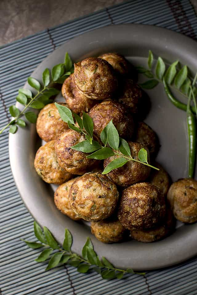 Pewter plate with South Indian style aebleskivers topped curry leaves and chilies