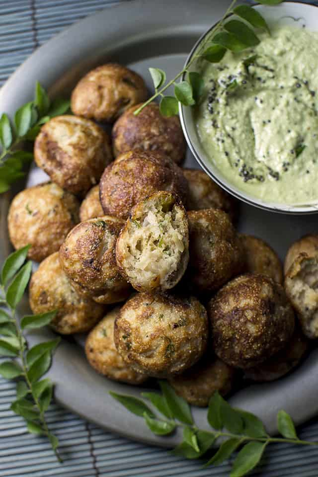 Pewter plate with a stack of south Indian savory aebleskivers and green chutney