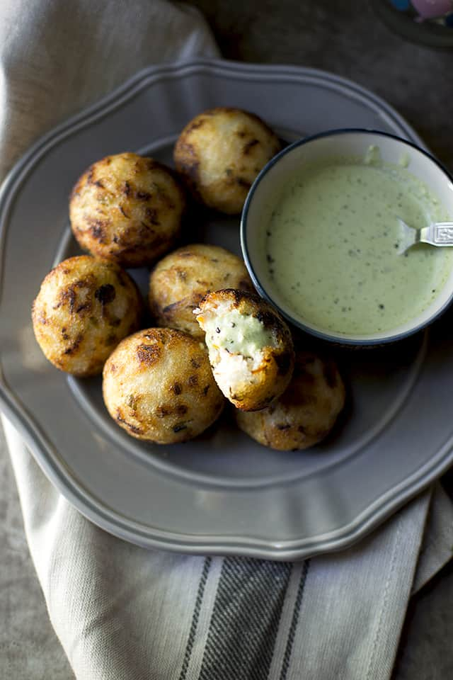 Grey plate with south indian savory aebleskivers with a small bowl of chutney