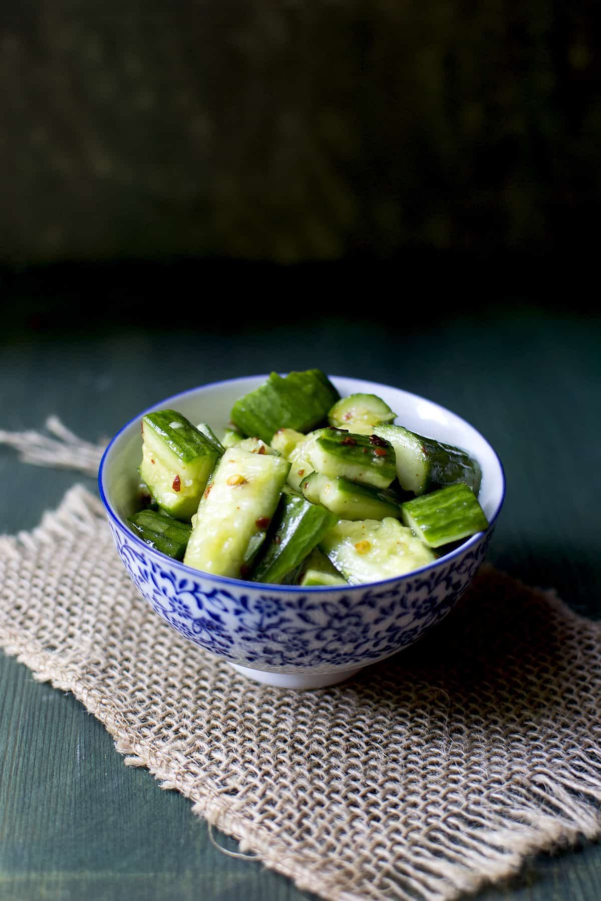 white and blue bowl with smashed cucumber salad