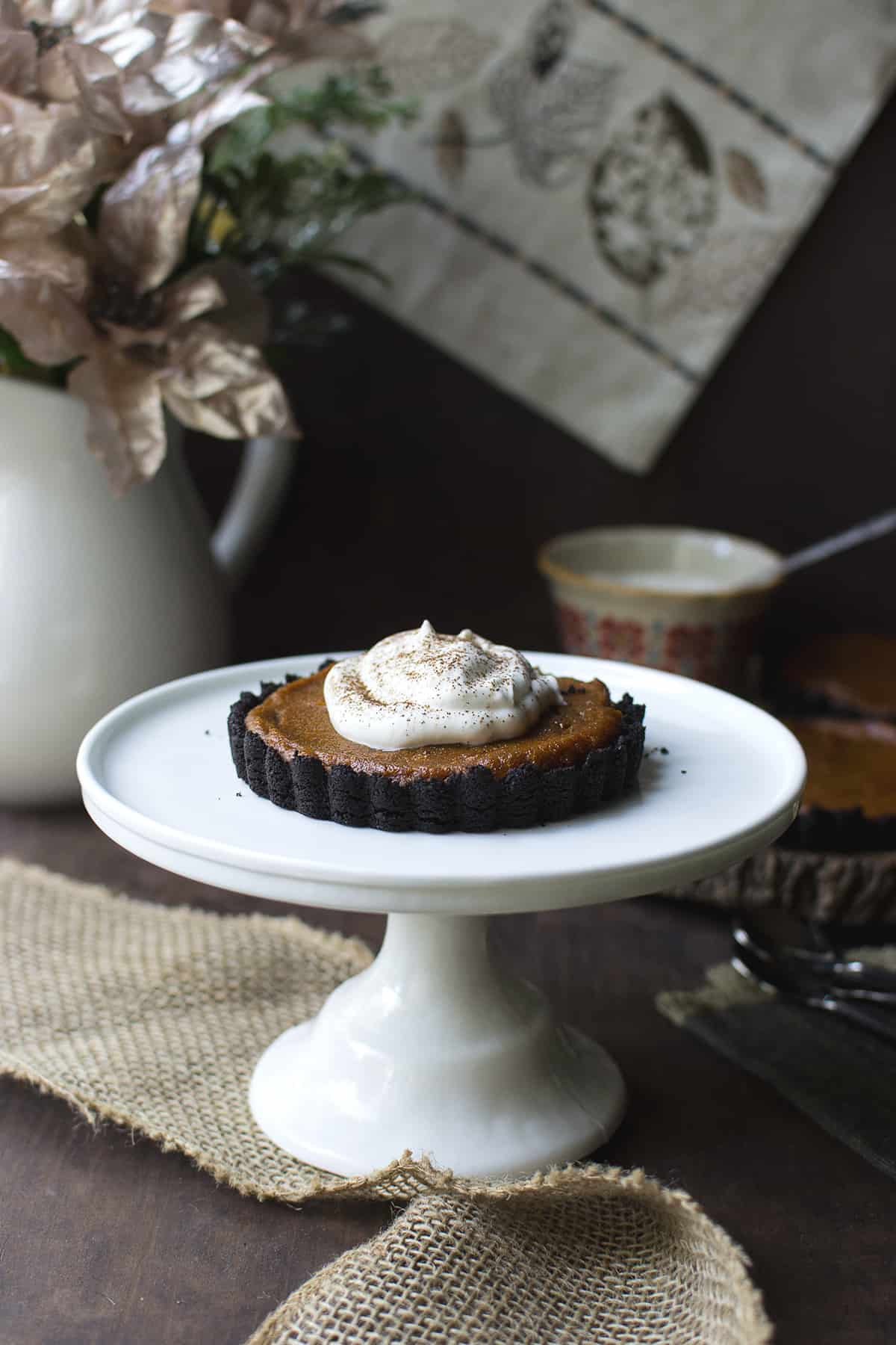White cake stand with a whipped cream topped mini pumpkin pie
