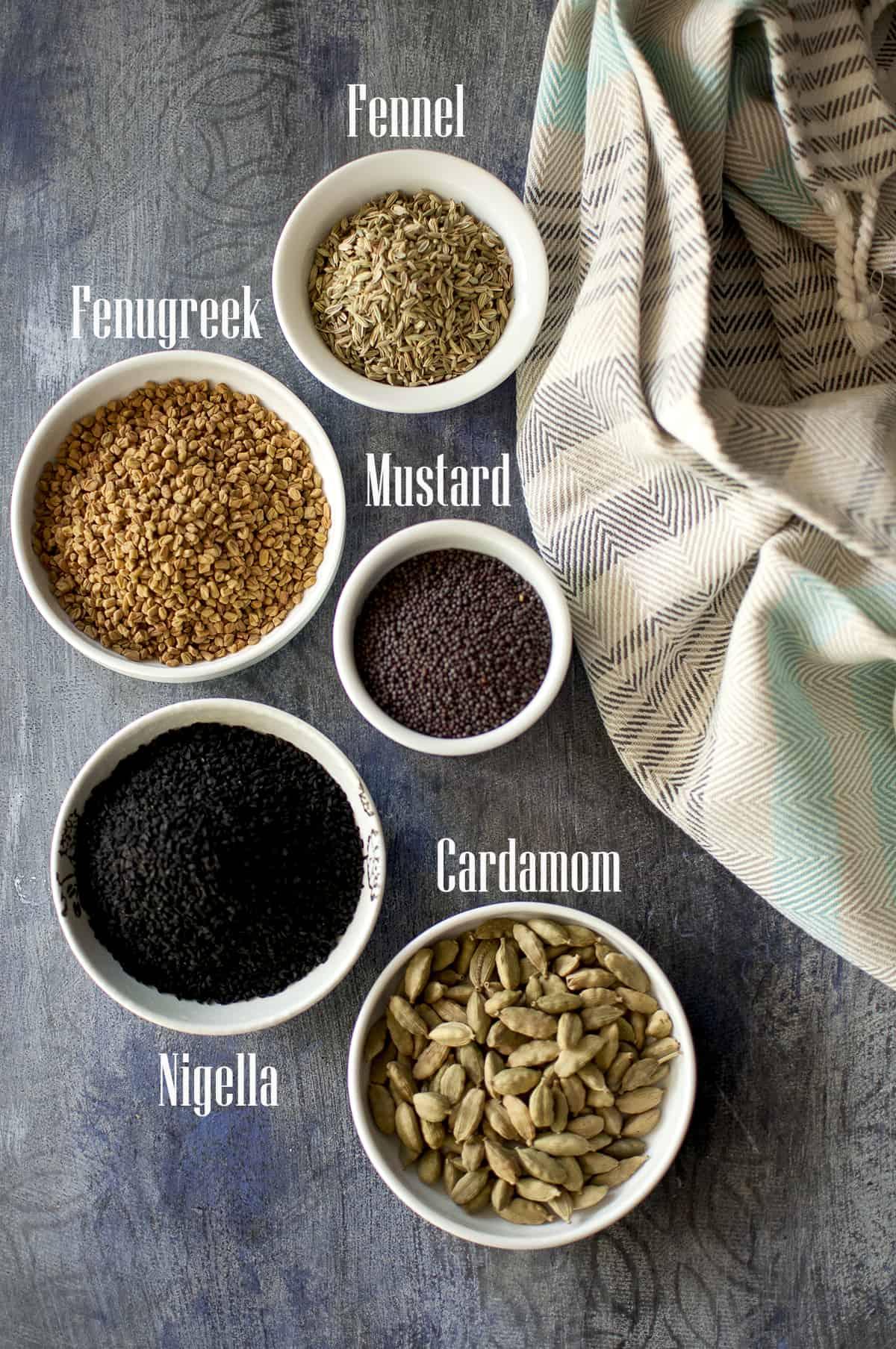 Spiced needed for the recipe placed in white bowls - Fennel, fenugreek, mustard, nigella, cardamom