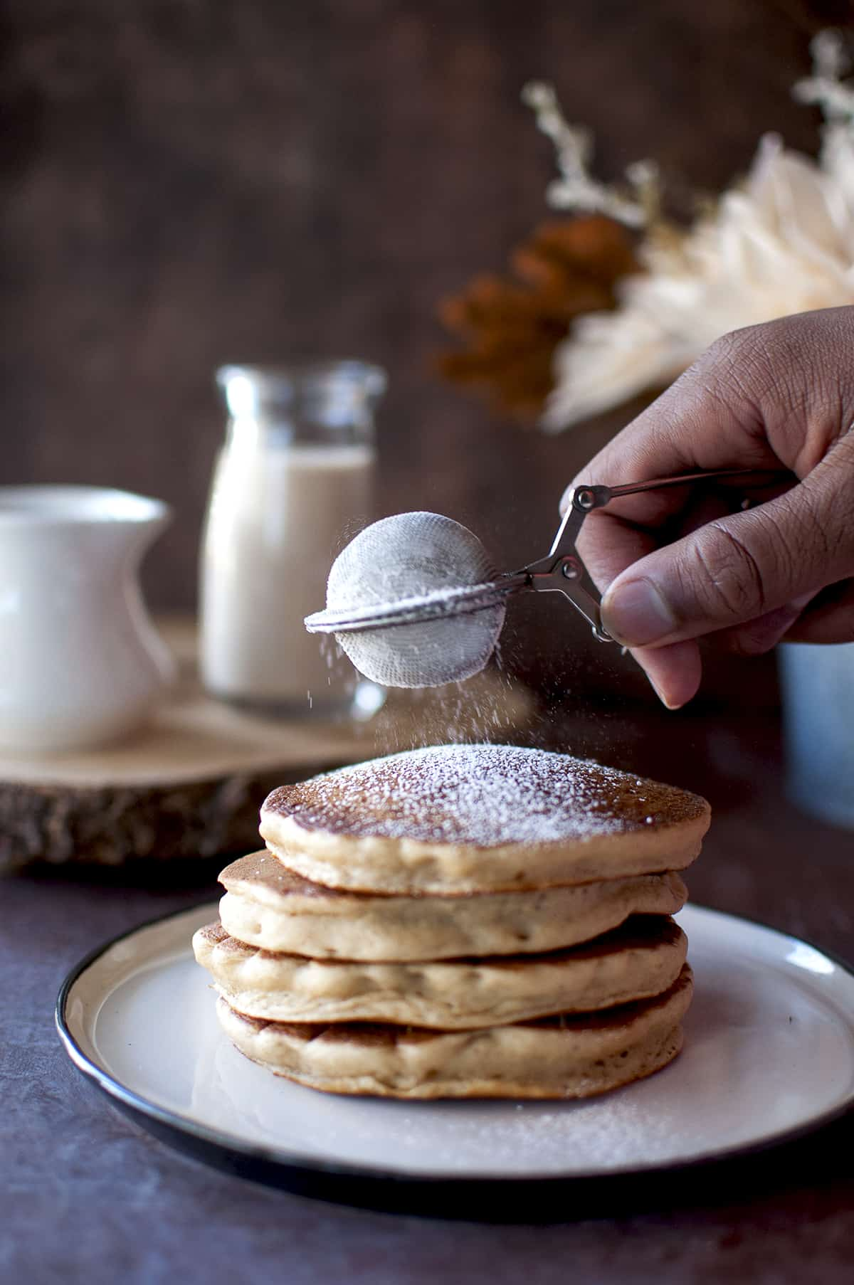 Hand sprinkling powdered sugar on a stack of pancakes