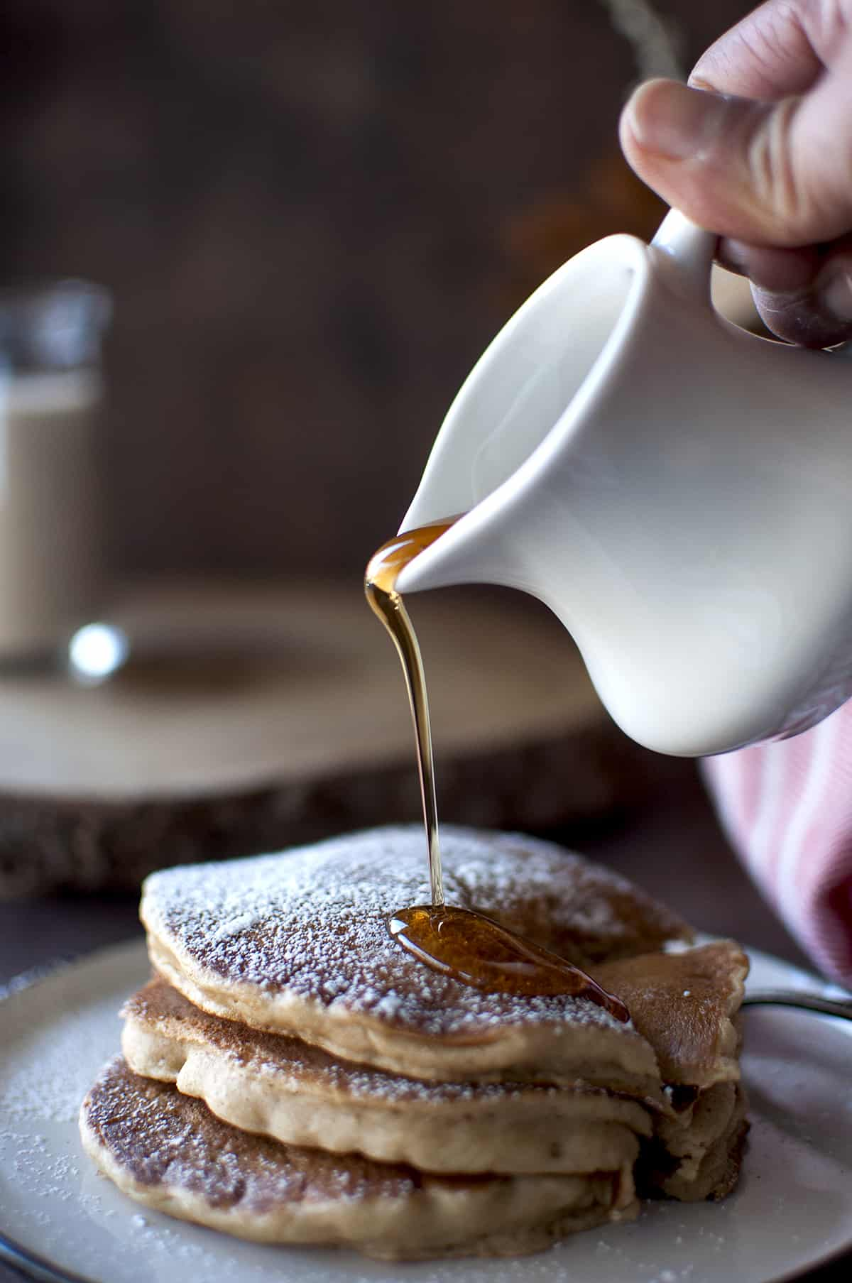Hand pouring maple syrup on stack of vegan eggnog pancakes