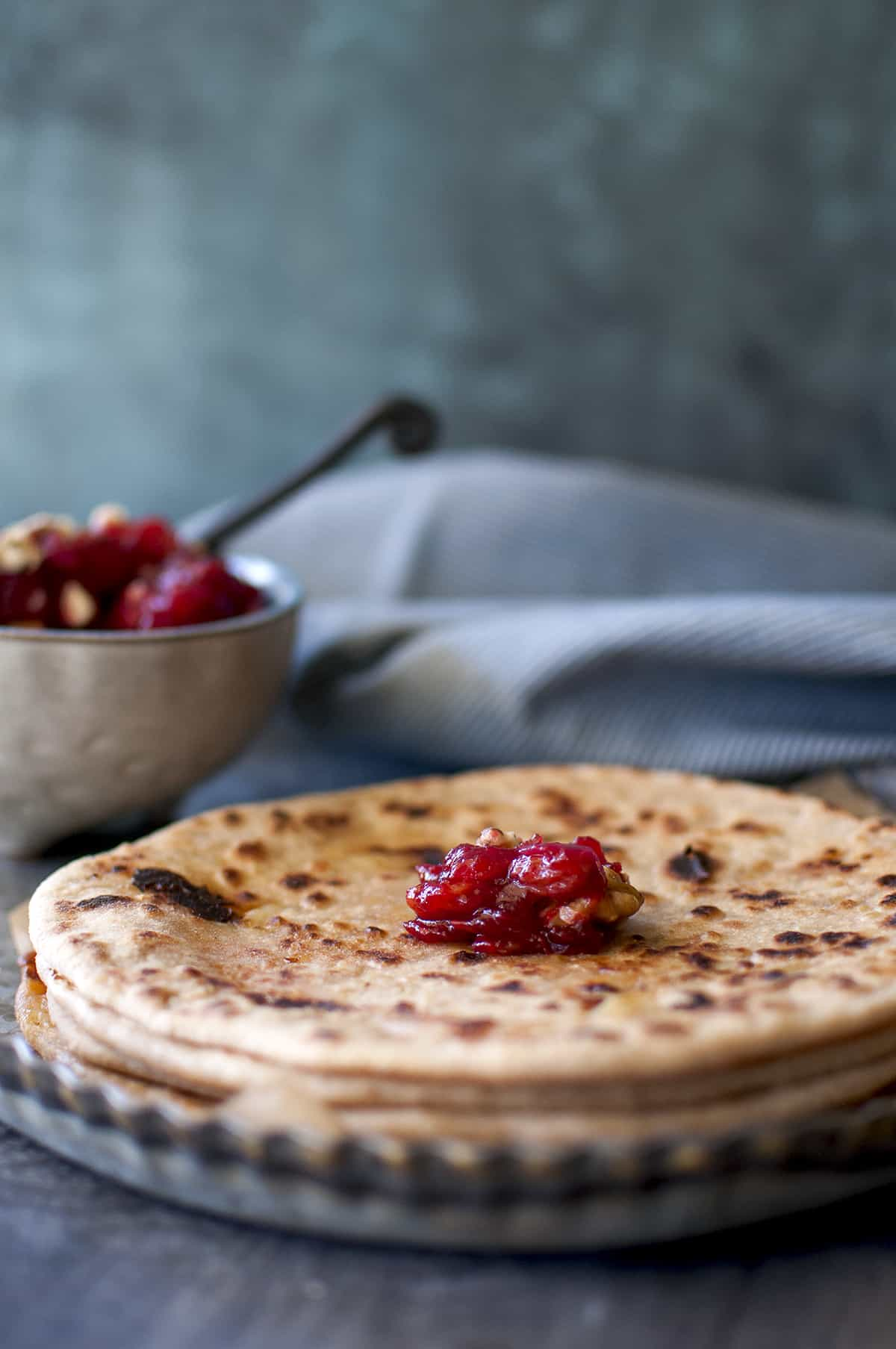 Stack of paratha topped with a dollop of cranberries chutney