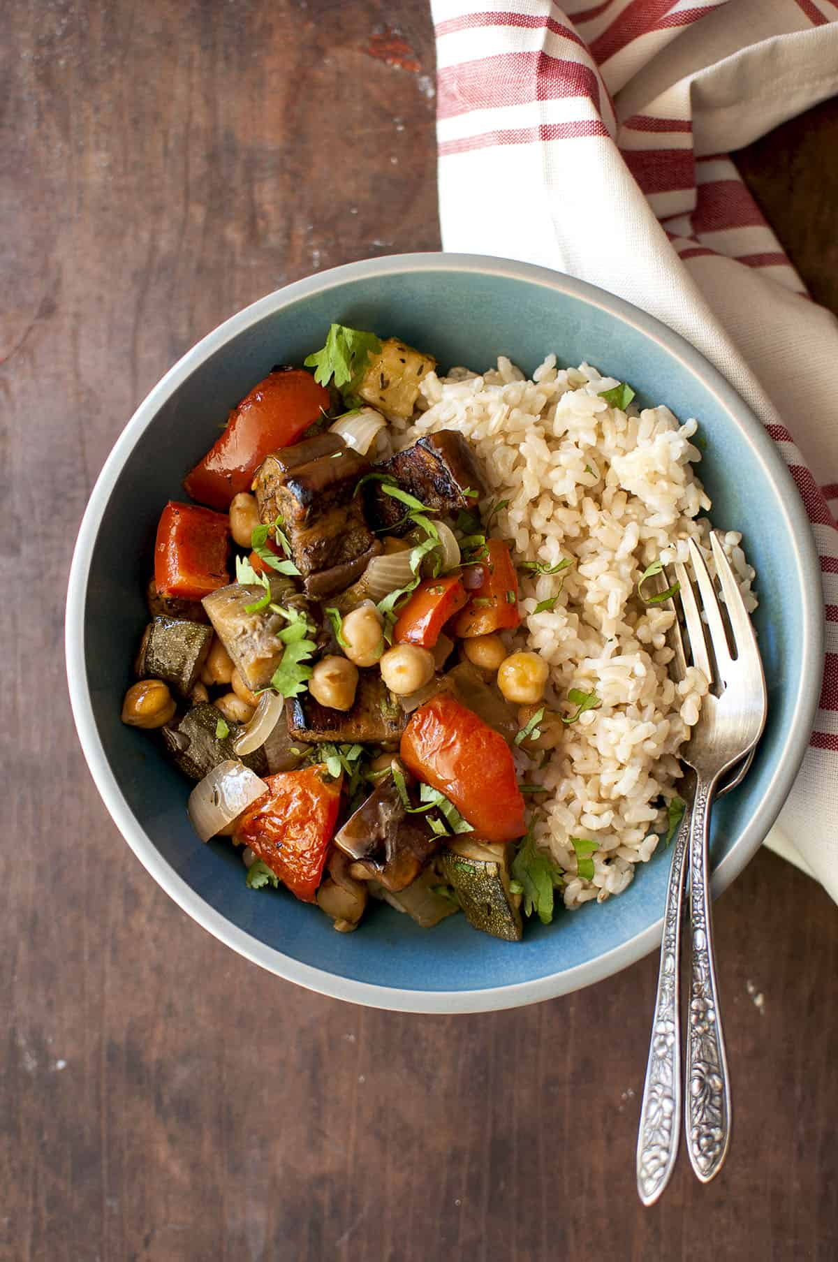Blue bowl with half roasted veggies and half brown rice