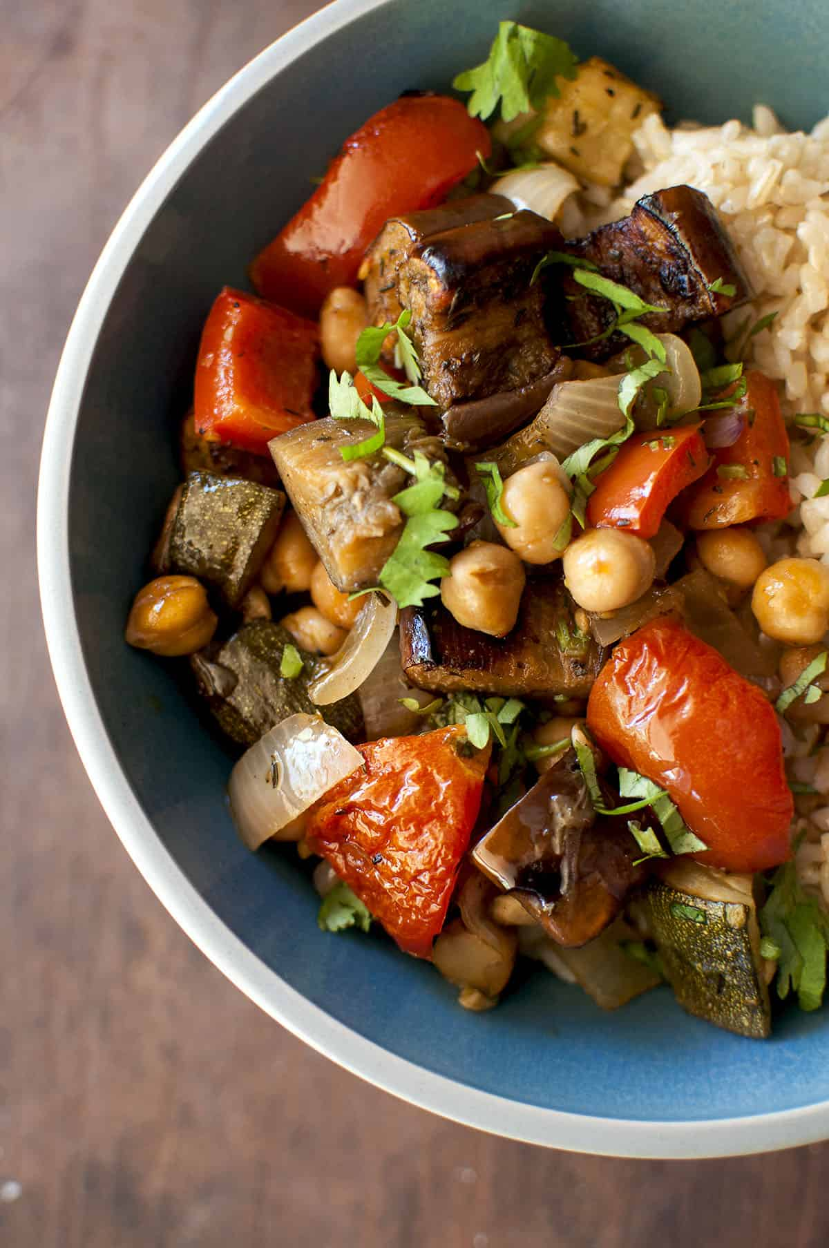 Grey bowl with roasted ratatouille garnished with fresh herbs
