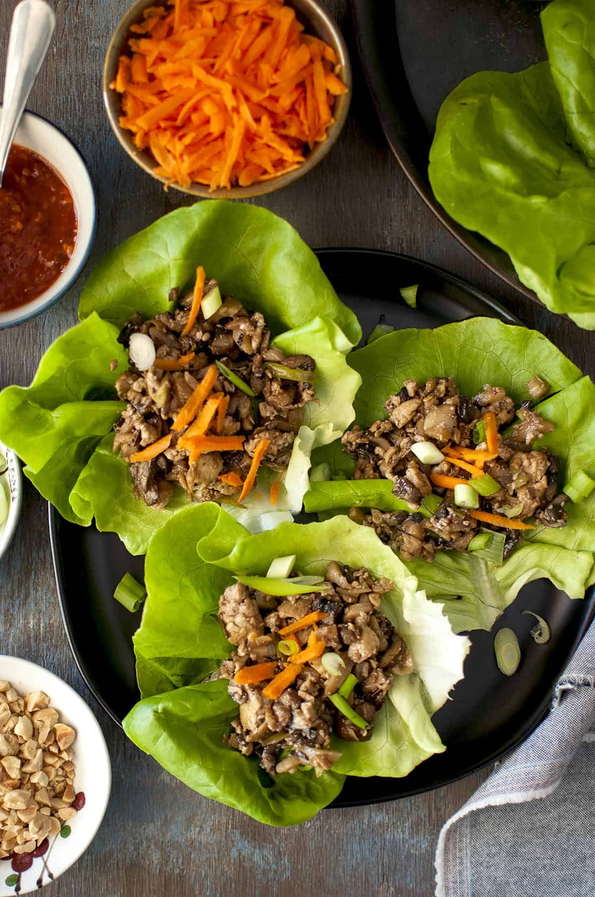 Tray with Tofu lettuce wraps topped with carrot and peanuts
