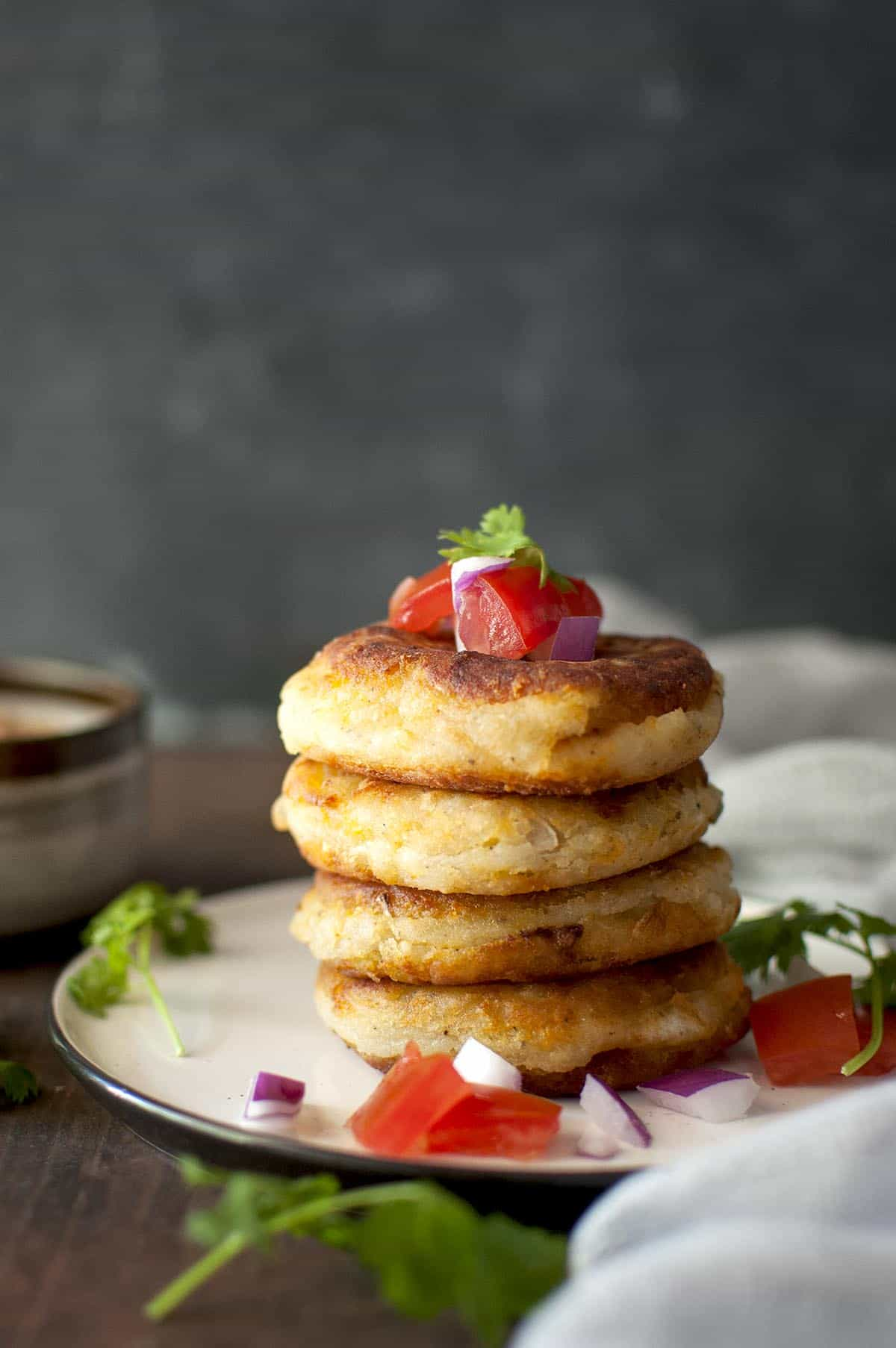 White plate with a stack of 4 Llapingachos topped with chopped tomatoes