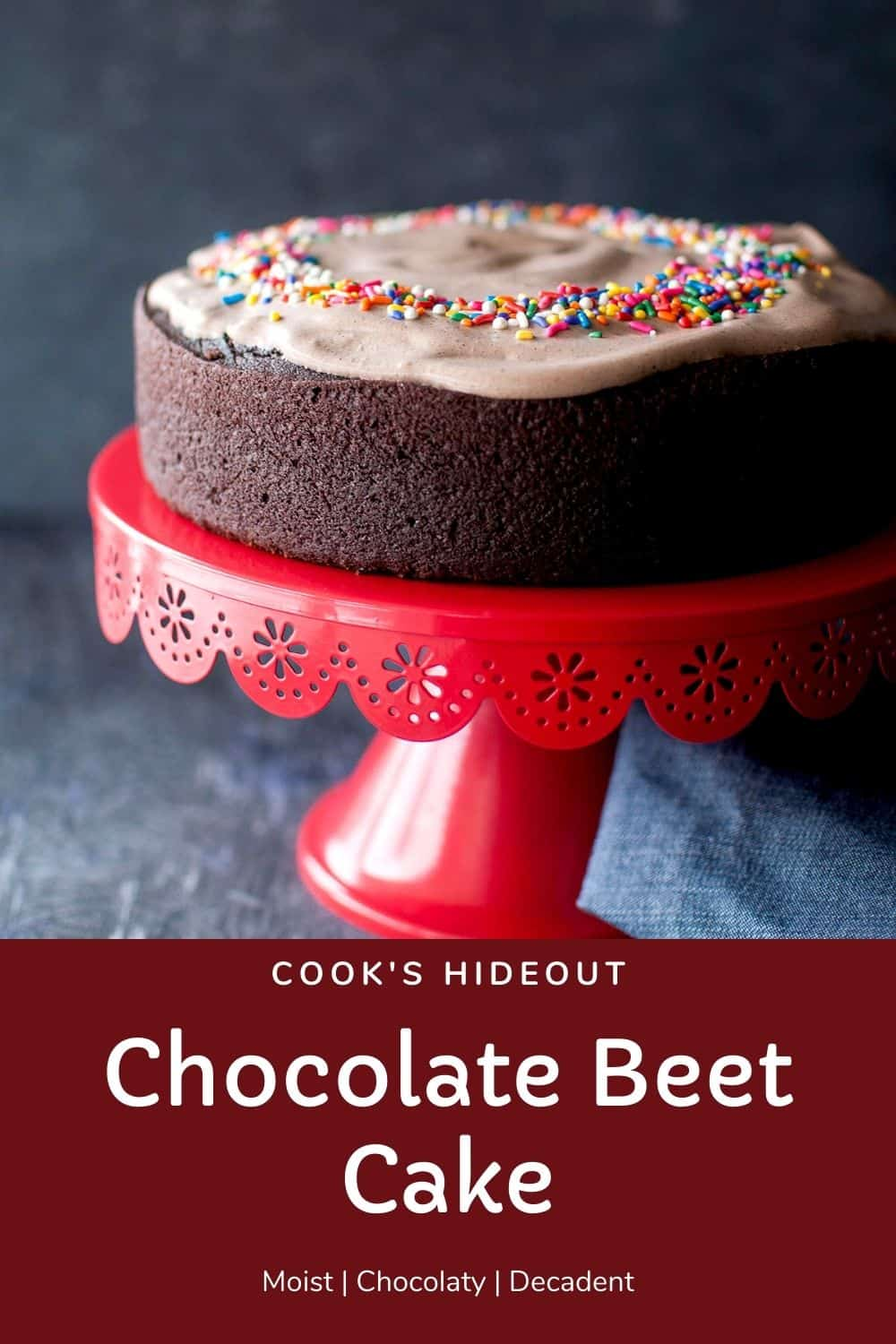Red cake stand with the vegan chocolate beet cake topped with chocolate frosting and sprinkles
