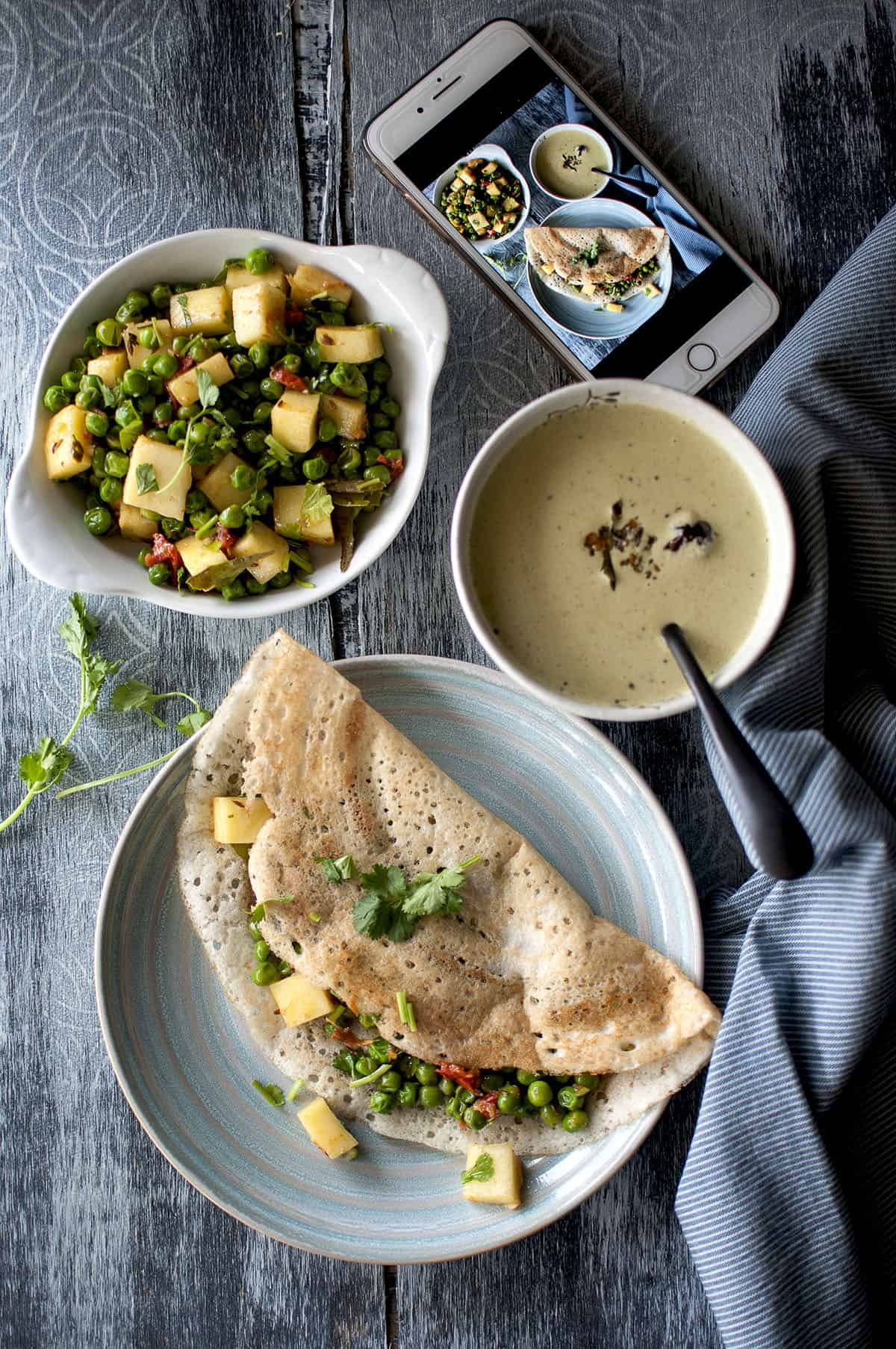Blue plate with folded Indian crepe with paneer cubes and green peas