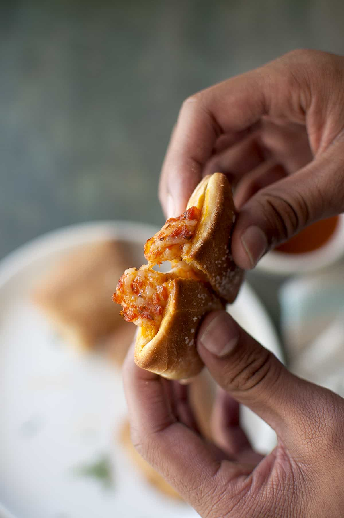 Hands holding cheesy pizza poppers