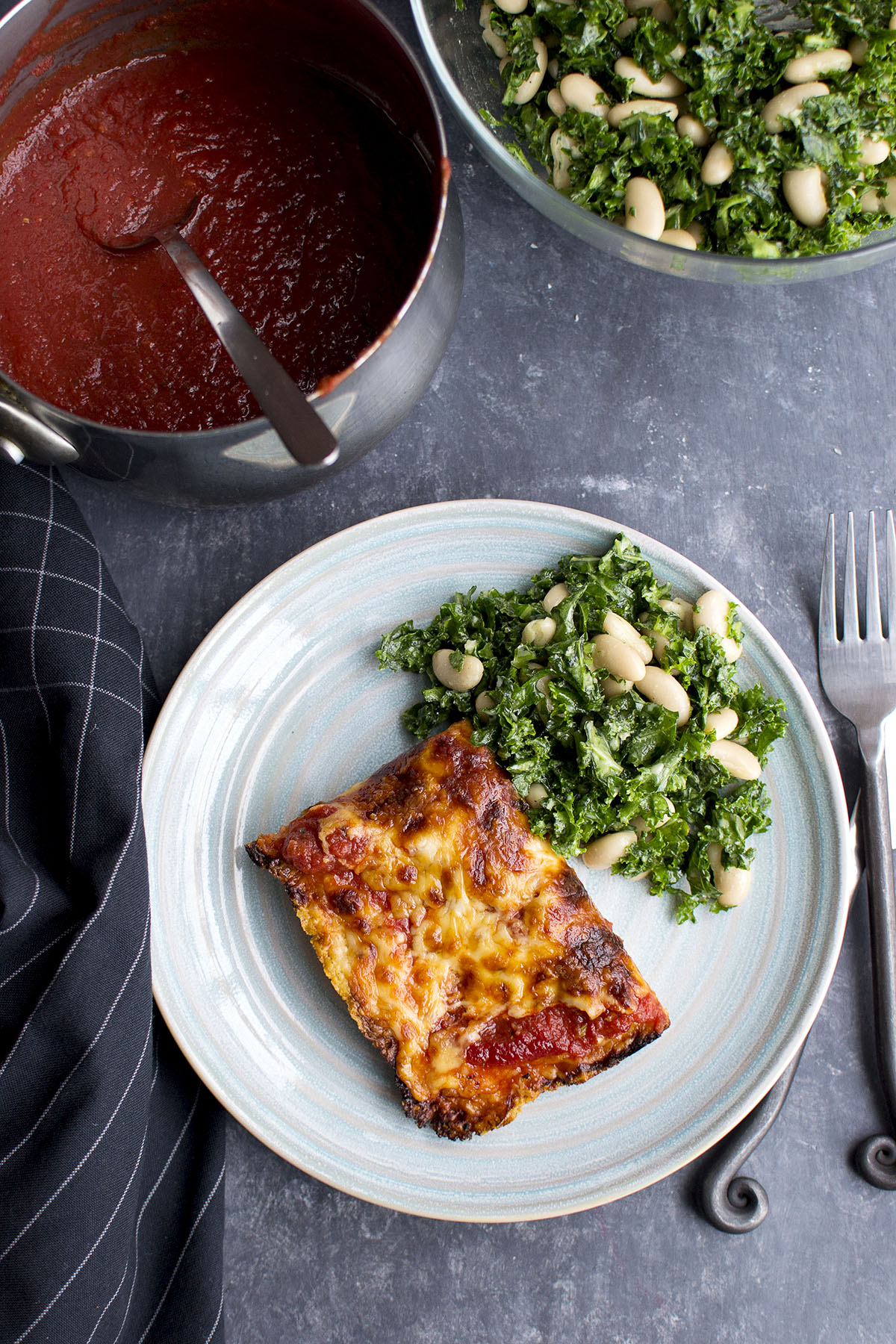 Blue plate with Detroit Style pizza slice and green salad