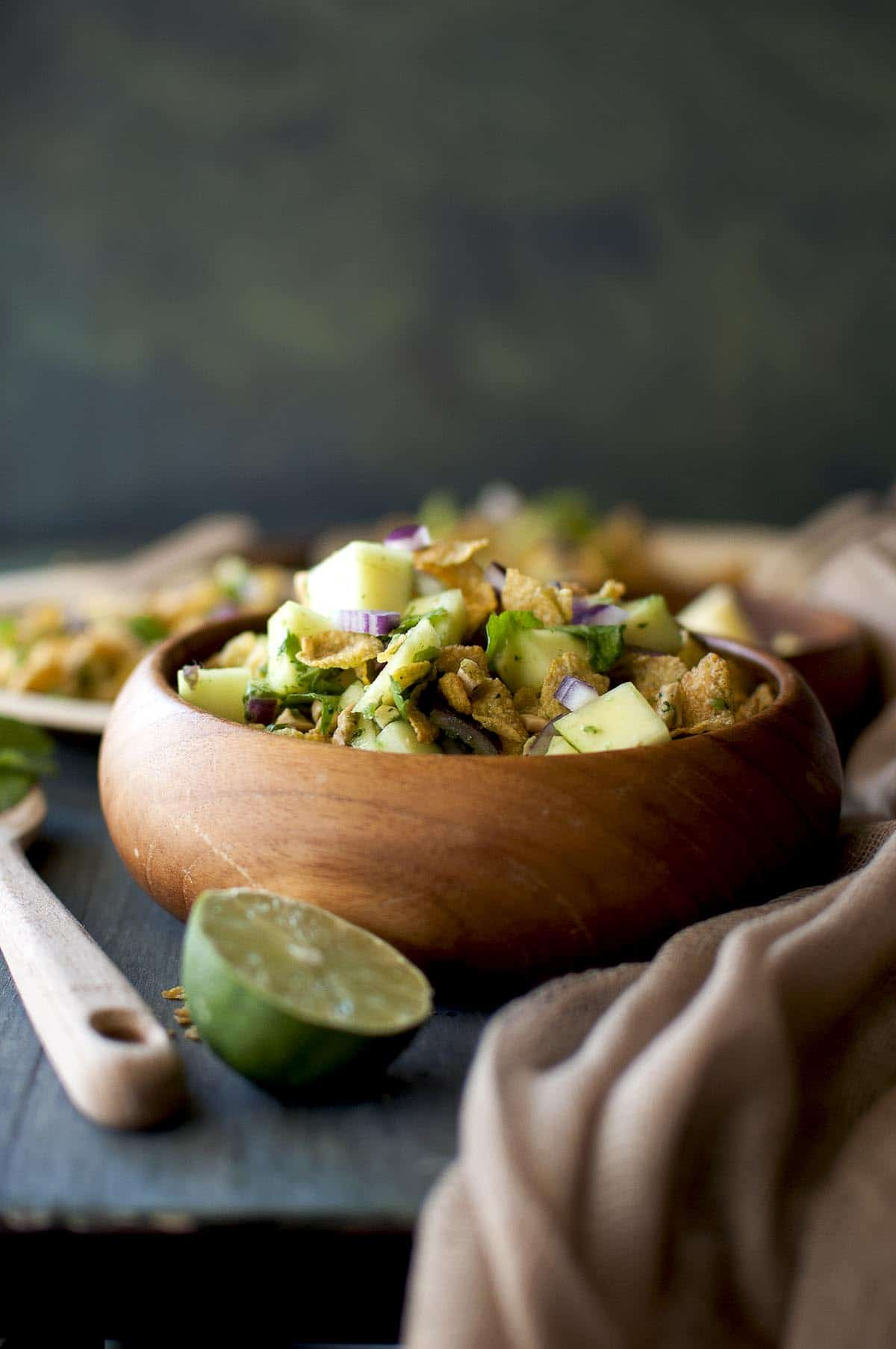 Wooden bowl with raw mango and corn flakes salad
