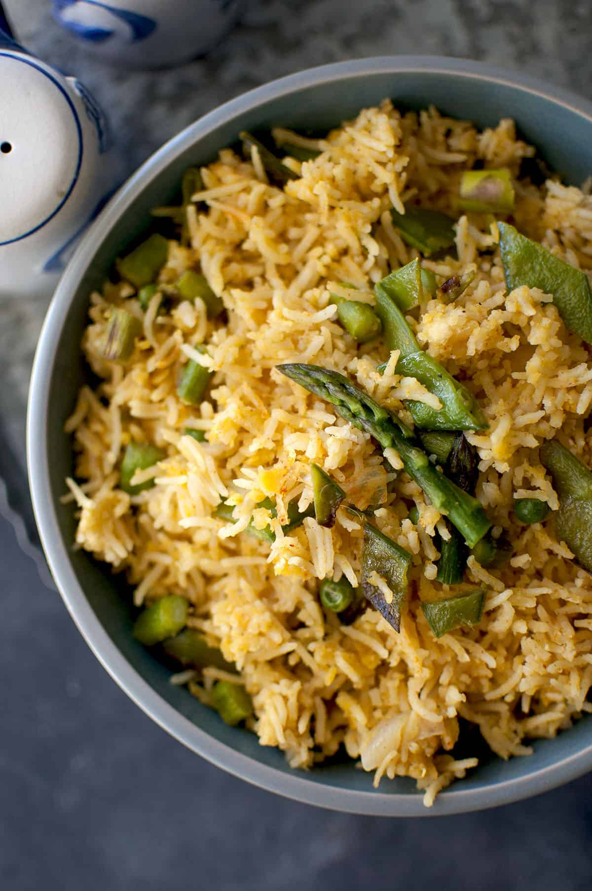 Blue bowl with vegetable khichdi topped with asparagus spear