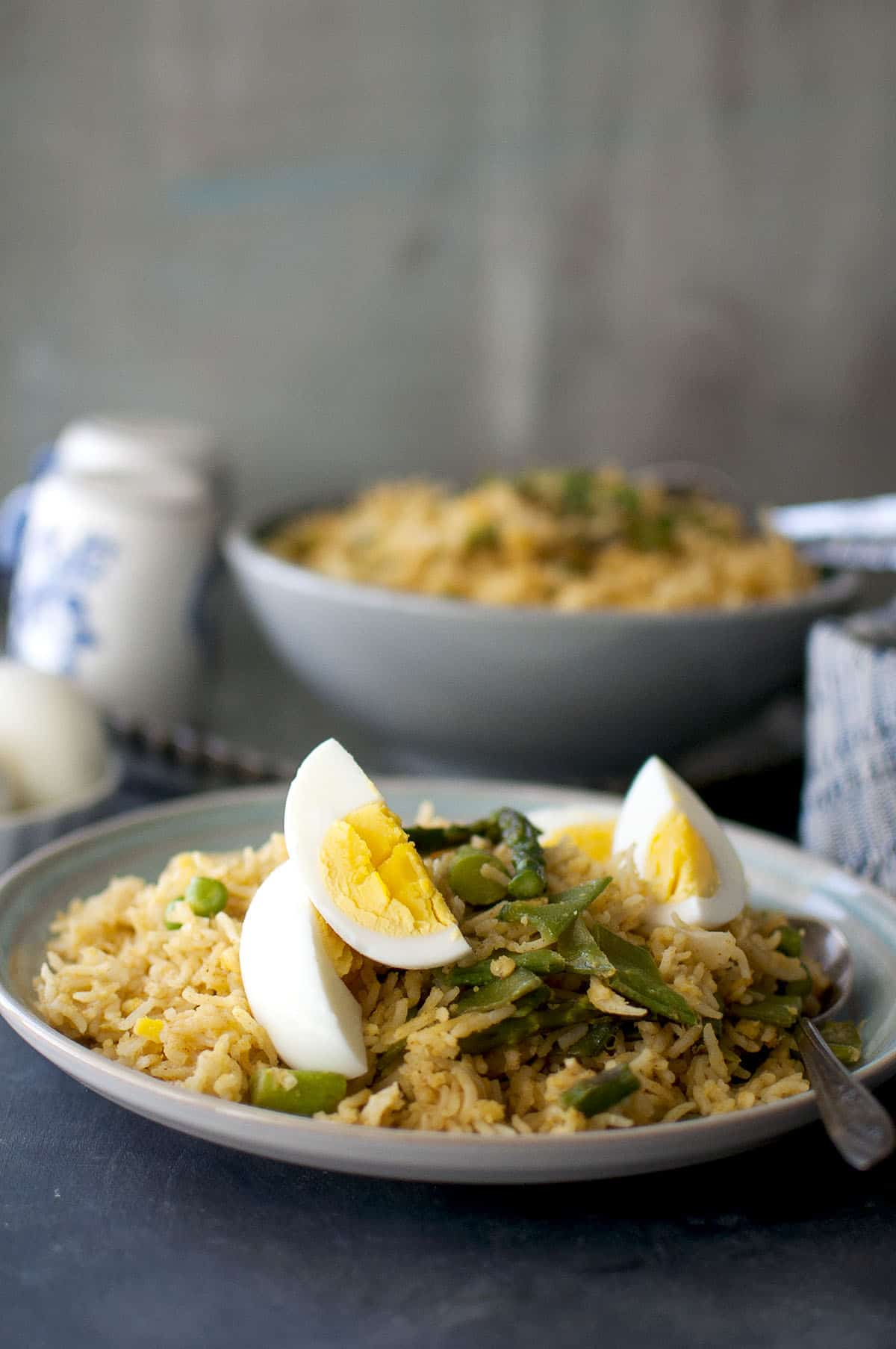 Blue plate with vegetarian kedgeree topped with asparagus and boiled eggs
