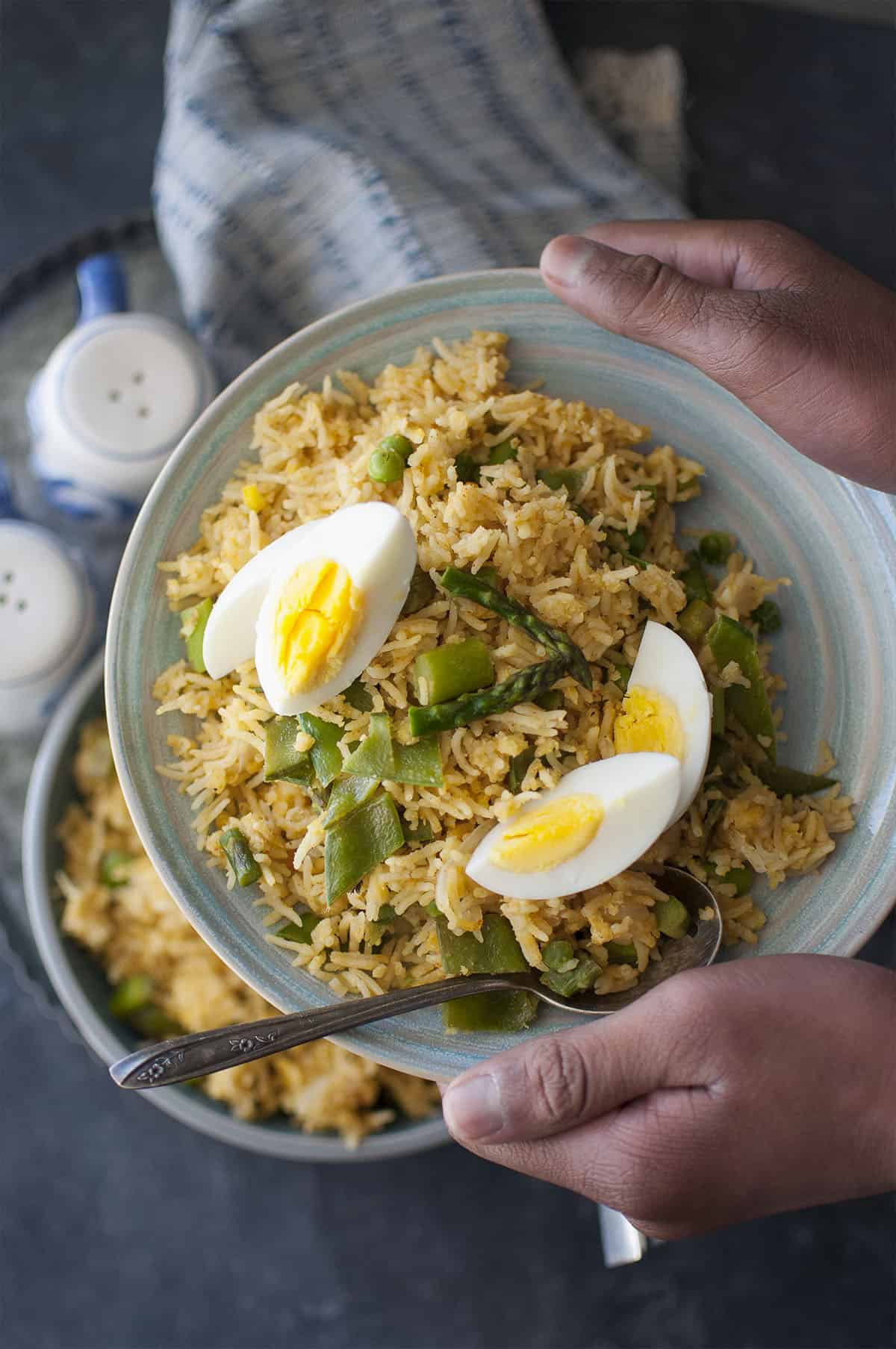 Hand holding blue plate with kedgeree topped with boiled eggs