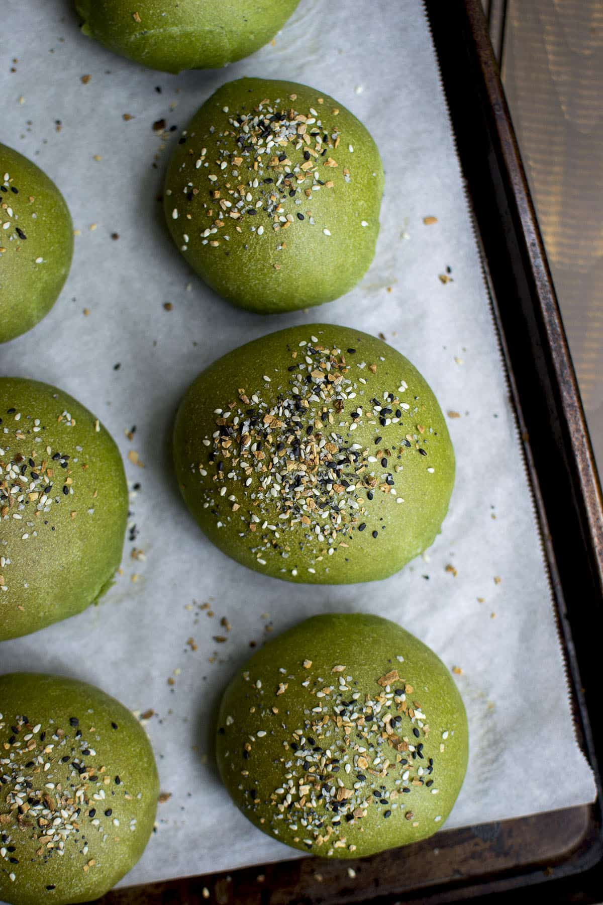 Parchment lined baking sheet with spinach flavored dinner rolls