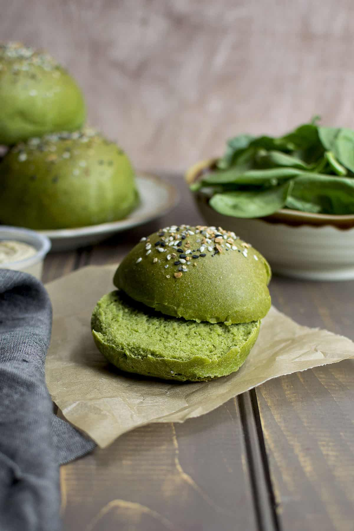 Slit spinach flavored sandwich roll on a parchment paper