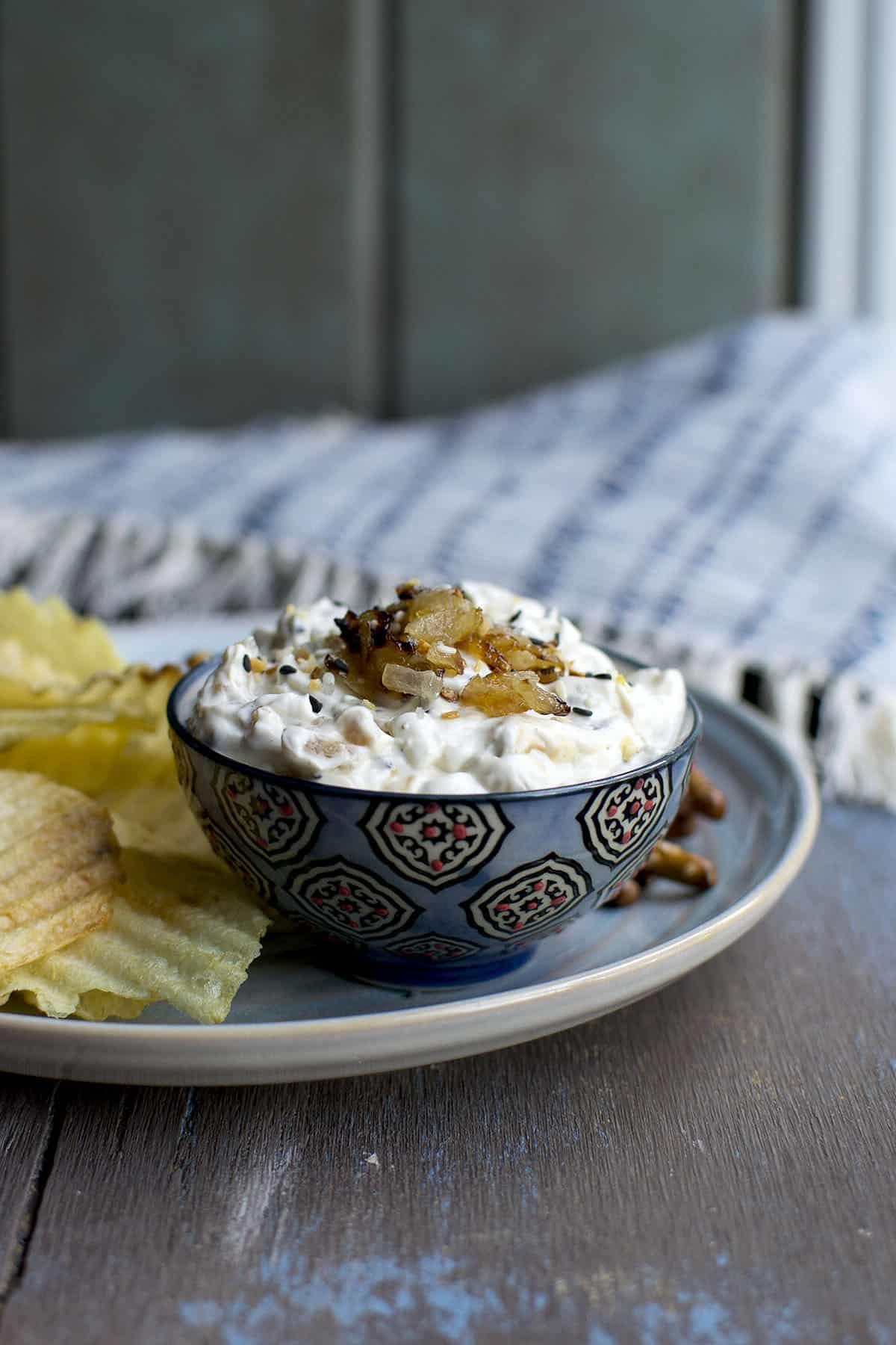 Blue bowl with creamy onion dip topped with caramelized onions