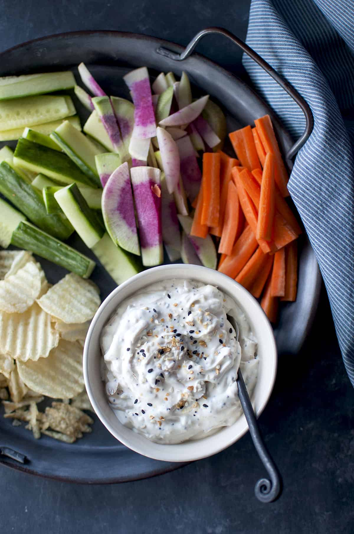 Tray with chopped veggies and a white bowl with bagel dip and a spoon