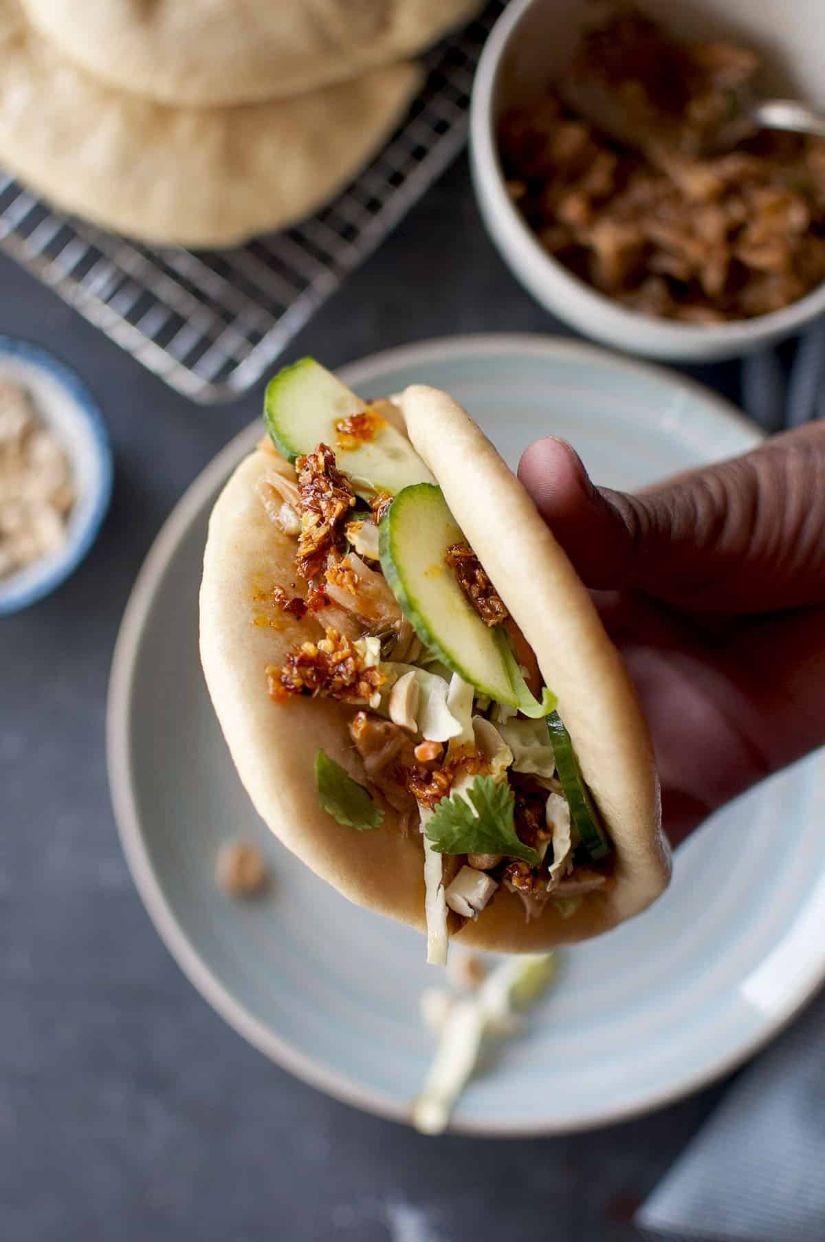 Hand holding steamed bun filled with jackfruit and veggies