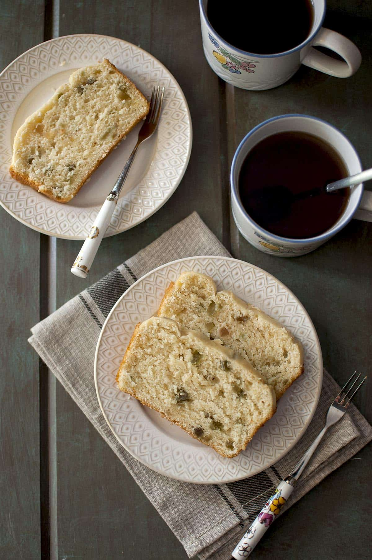 Two slices of Ice Cream bread on a white plate with mugs of tea in the background
