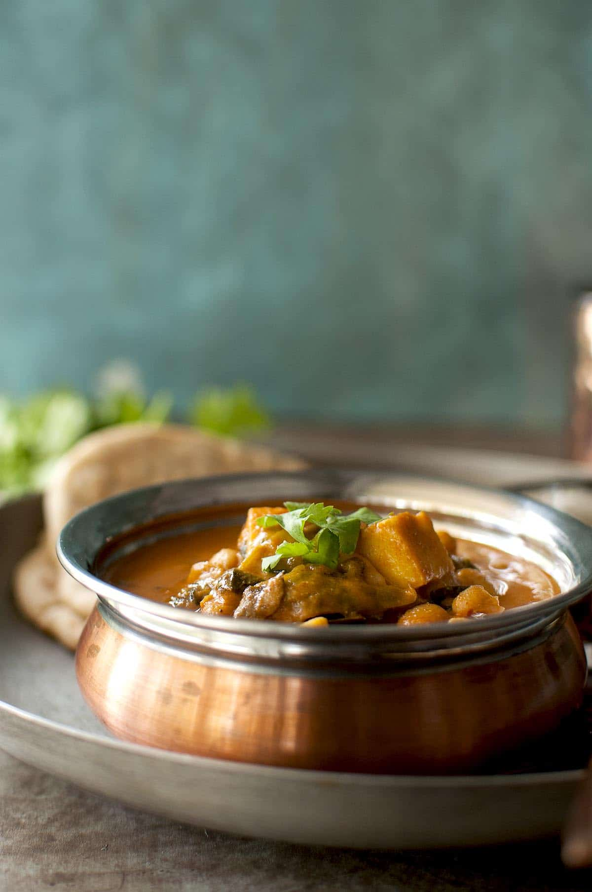 Copper bottom bowl with paneer curry with white beans