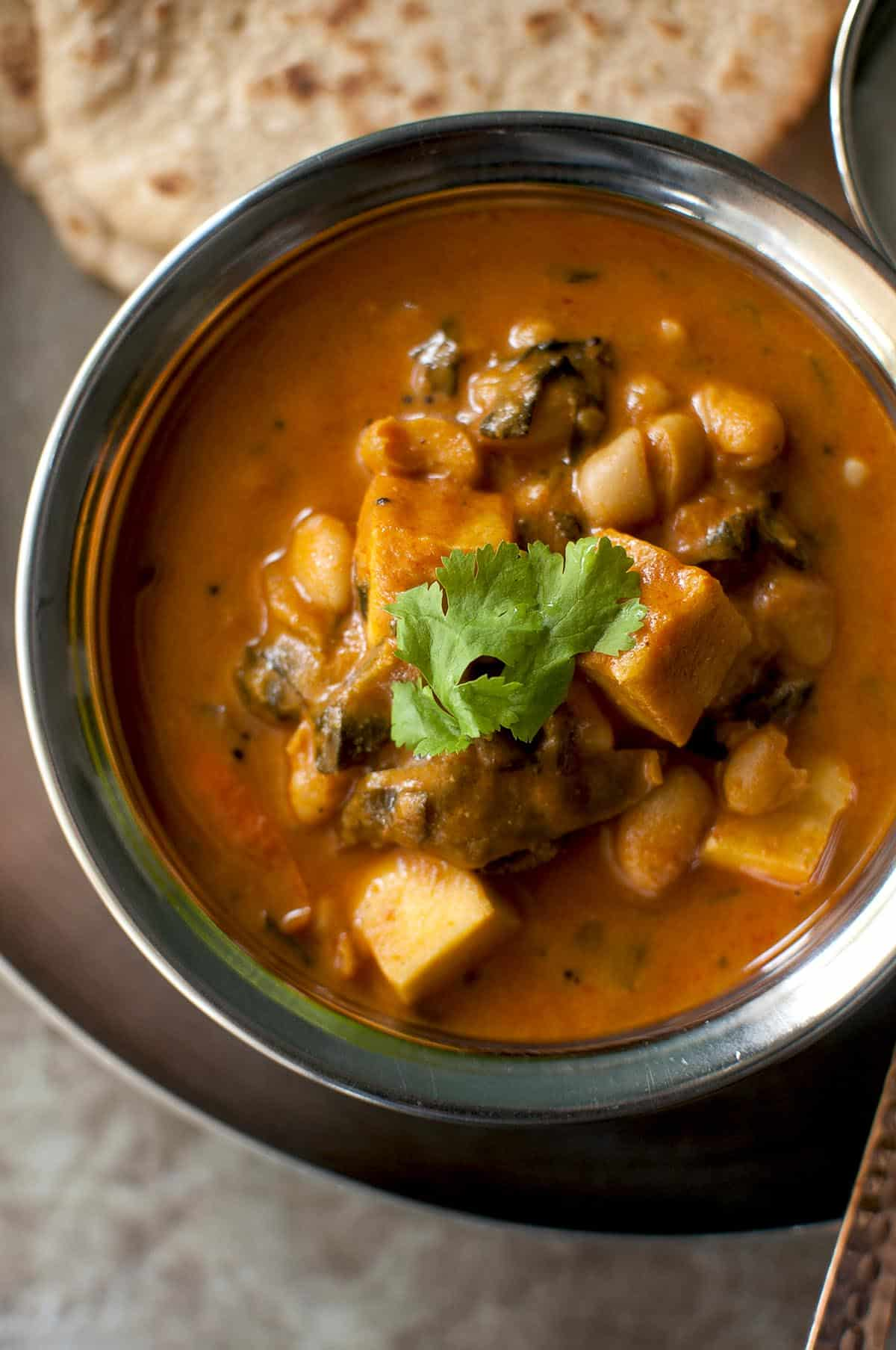 Top view of a steel bowl with paneer and white bean curry