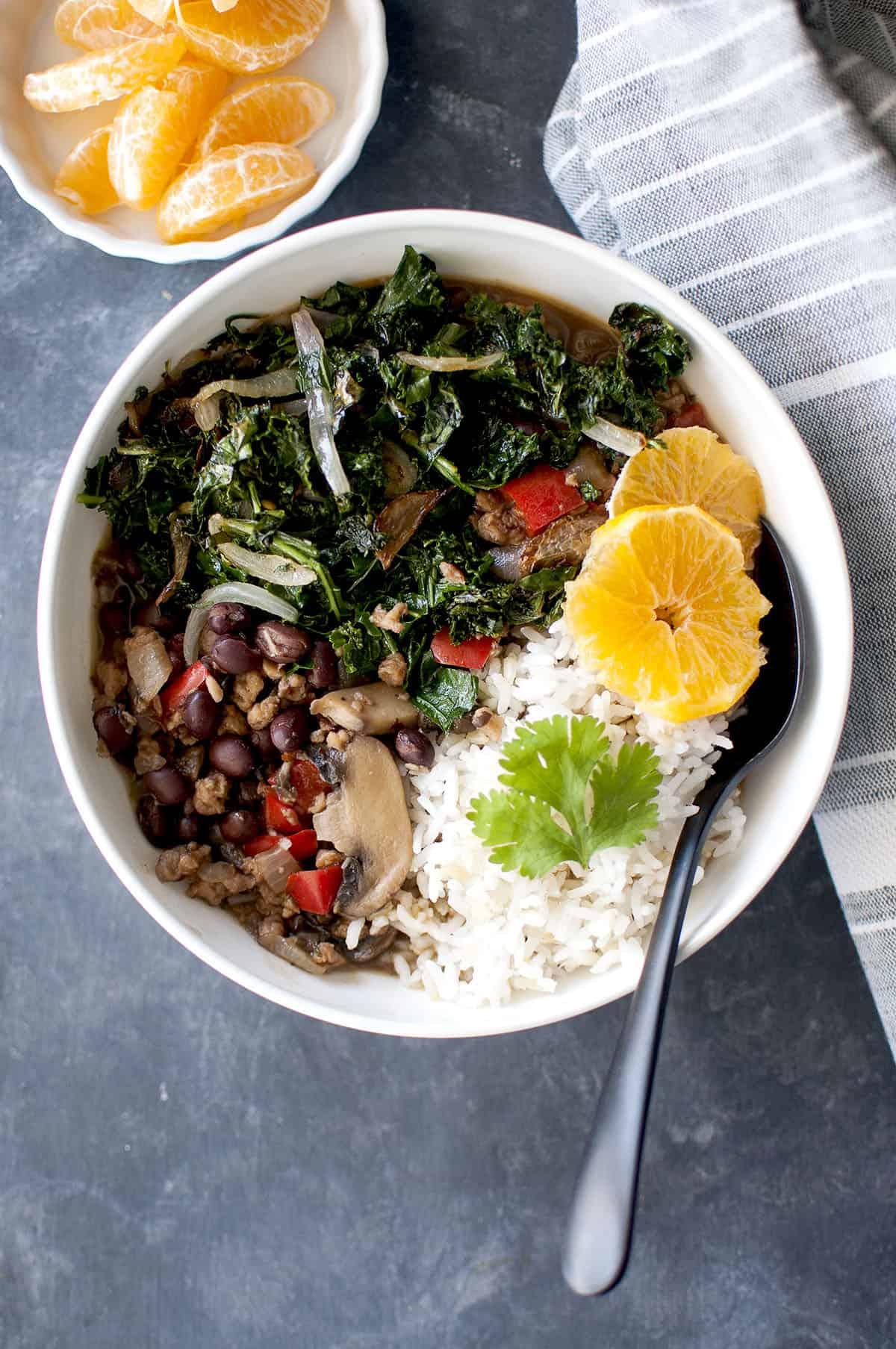 White bowl with Vegan Feijoada served with white rice and orange segments