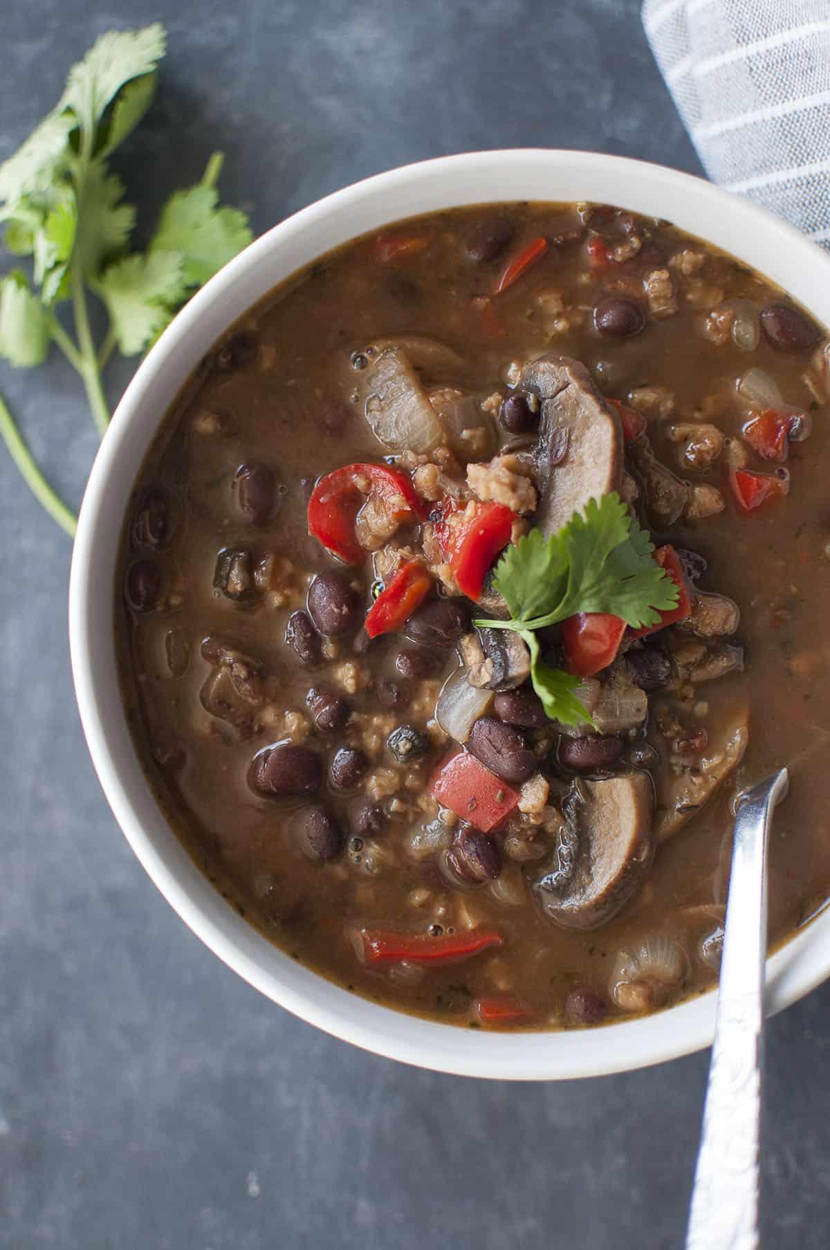 White bowl with chunky black bean stew topped with cilantro